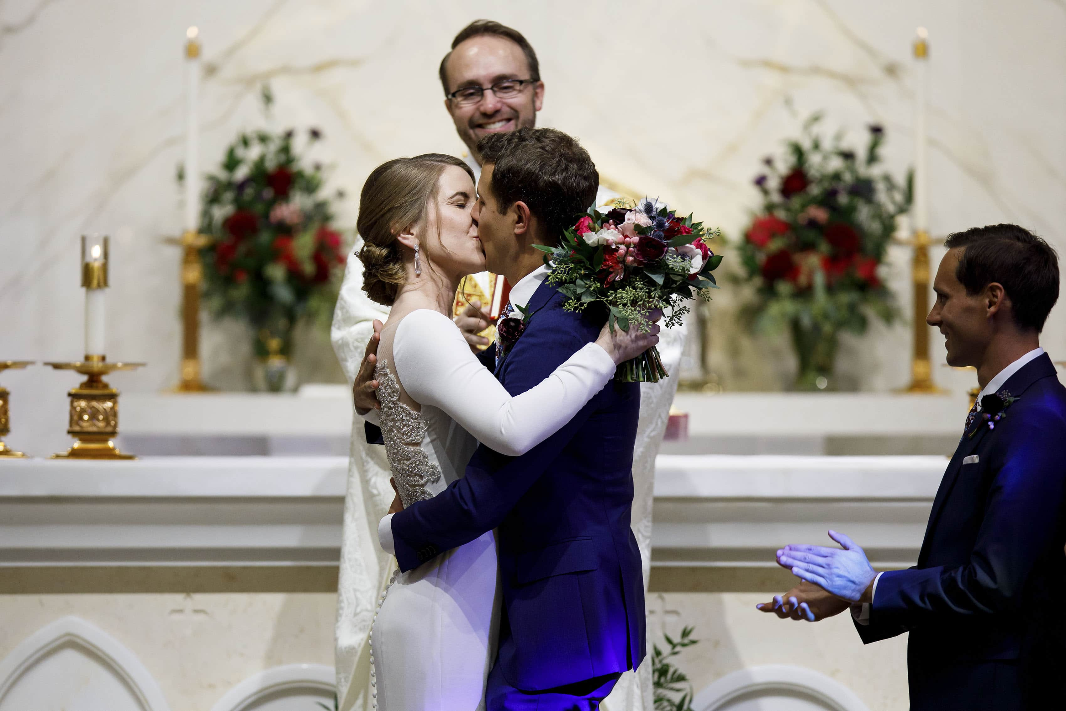 The couple share their first kiss during their wedding ceremony at Our Lady of Lourdes in Denver