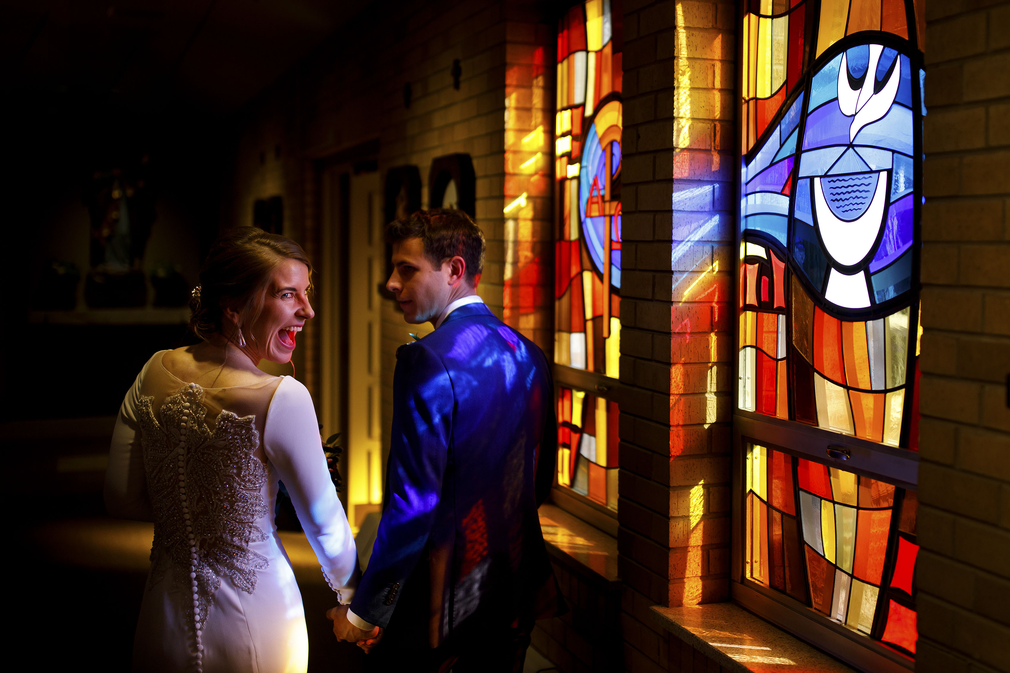The bride laughs while walking down the stained glass hallway with her husband during her wedding day