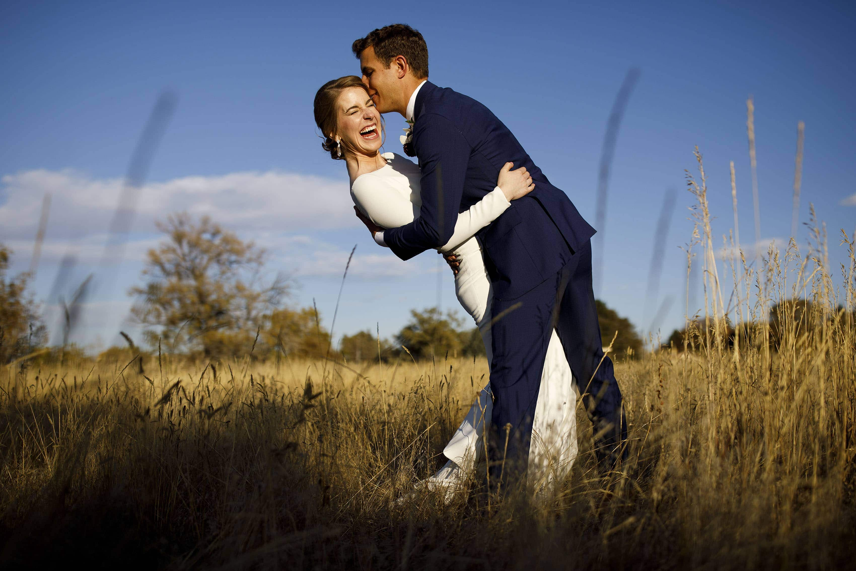 Mike kisses Jessica as she laughs while in a field at The Vista at Applewood Golf Course