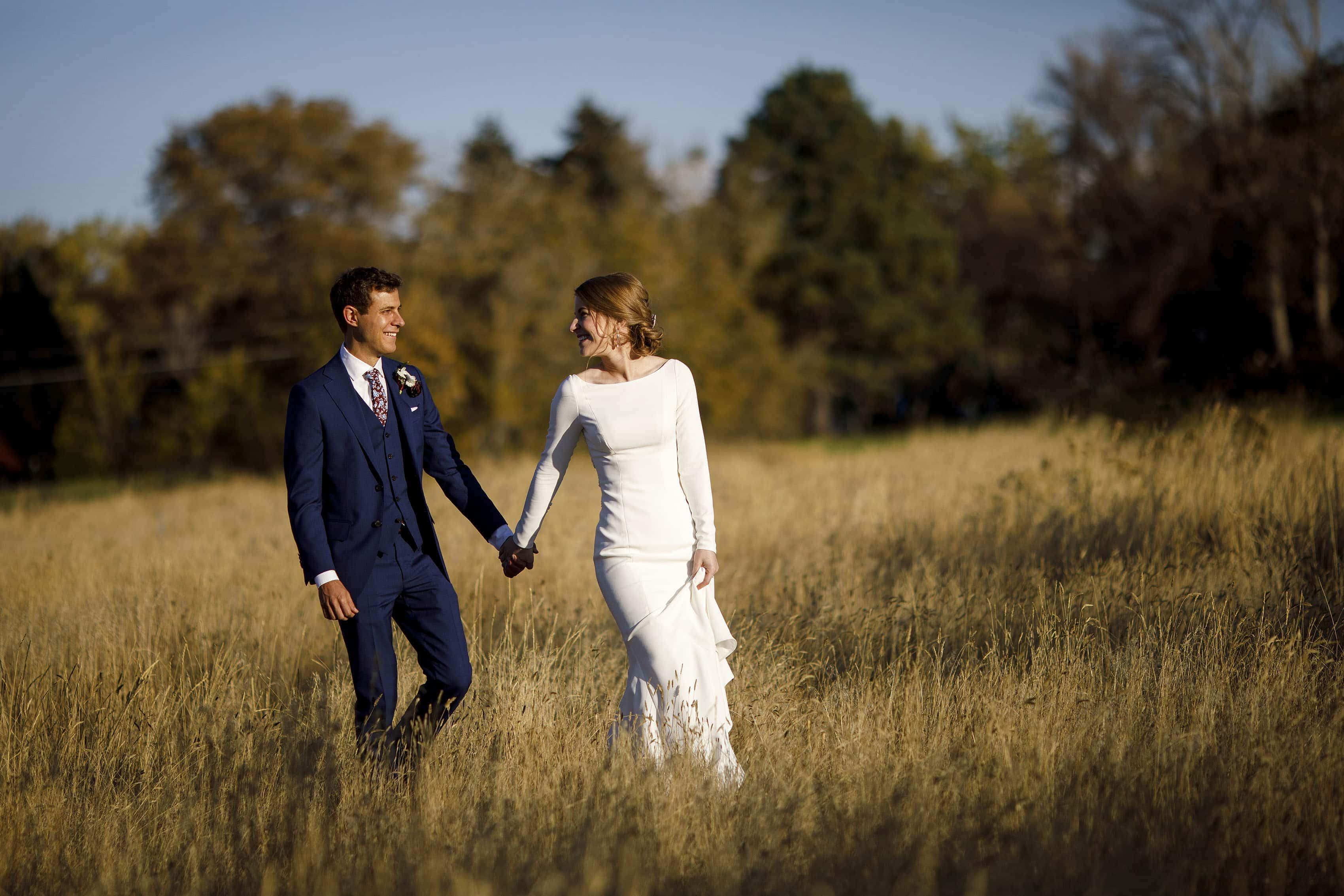 Mike and Jessica walk together in a field at The Vista at Applewood Golf Course on their wedding day