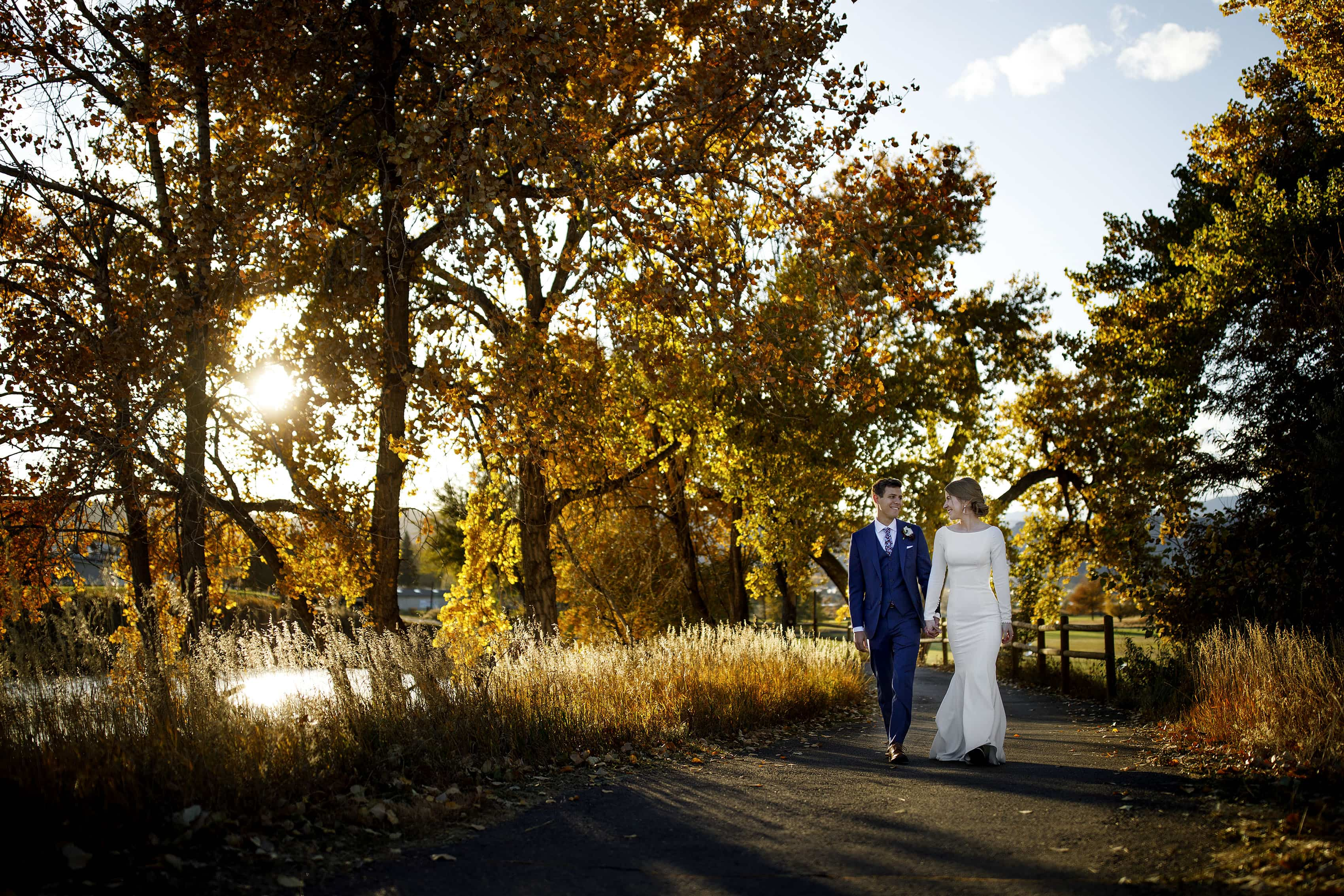 The newlyweds walk together near a colorful tree at The Vista at Applewood Golf Course on their wedding day