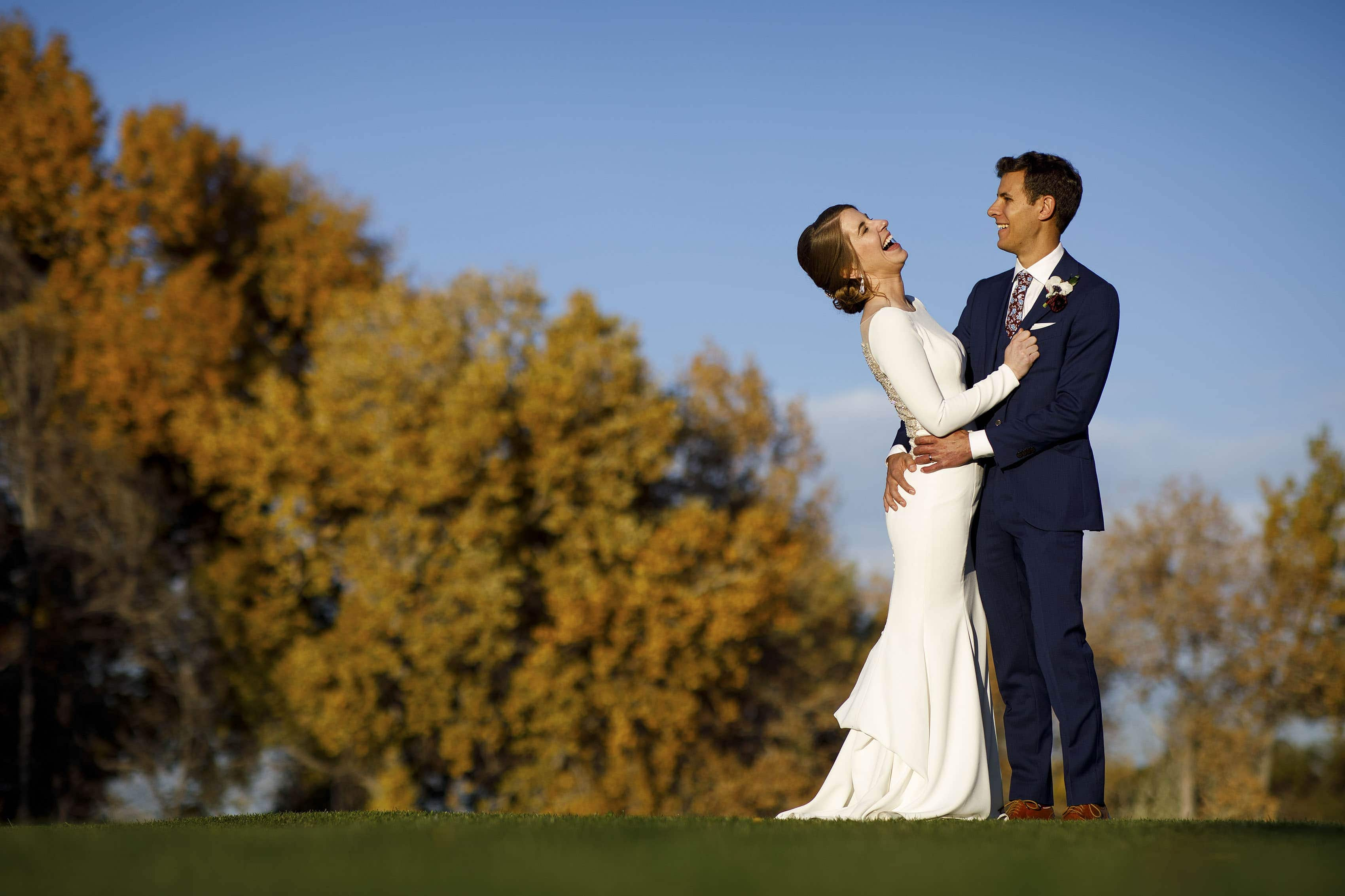 Jessica and Mike laugh outside during their wedding at The Vista at Applewood Golf Course
