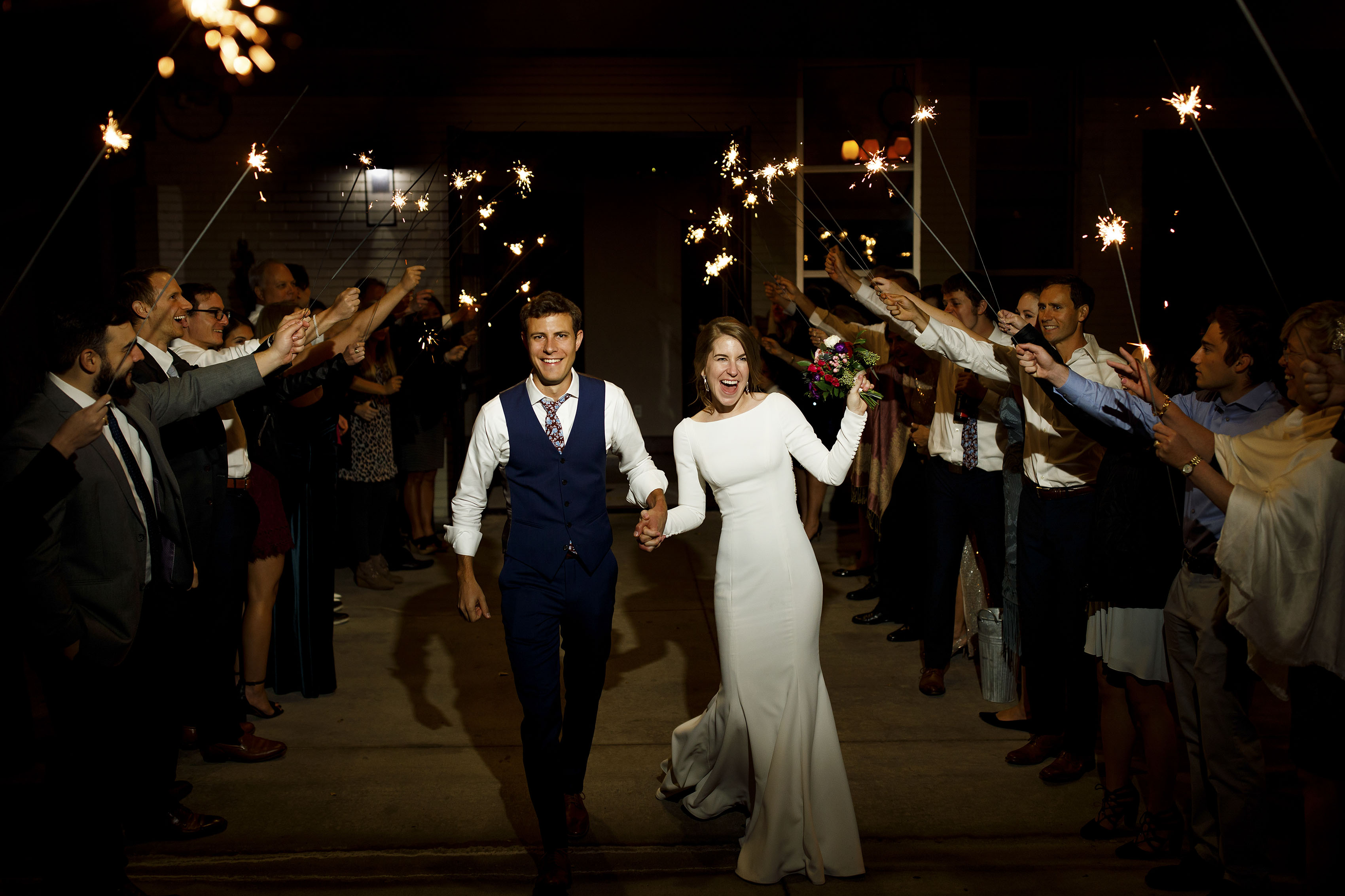The newlyweds smile during their sparkler exit following their wedding atThe Vista at Applewood Golf Course