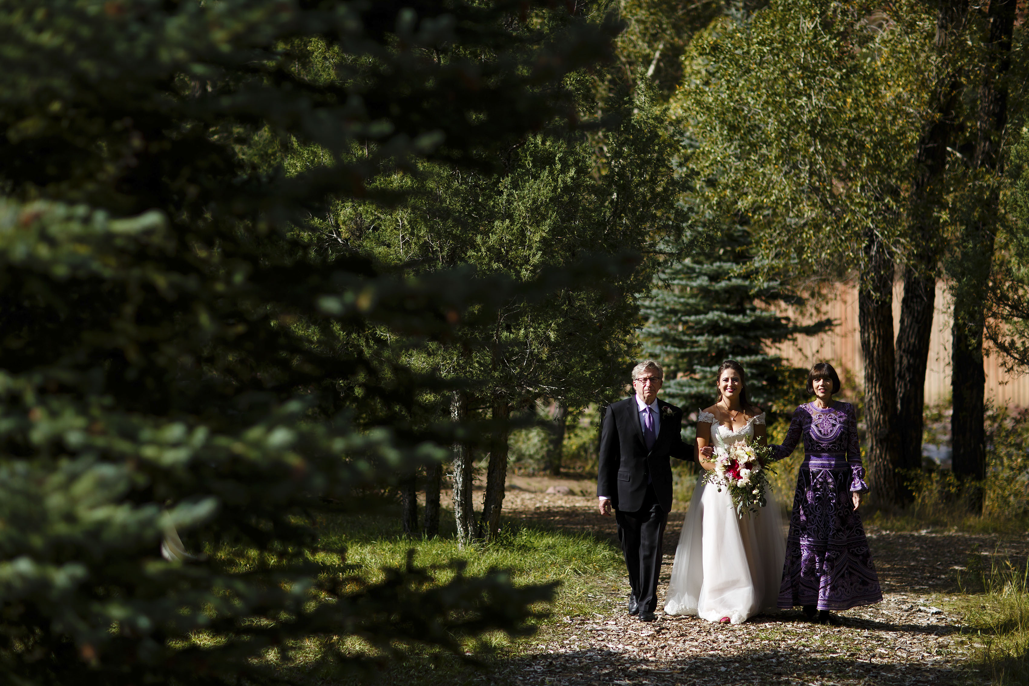 the bride walks with her parents at Snowmass Cottages