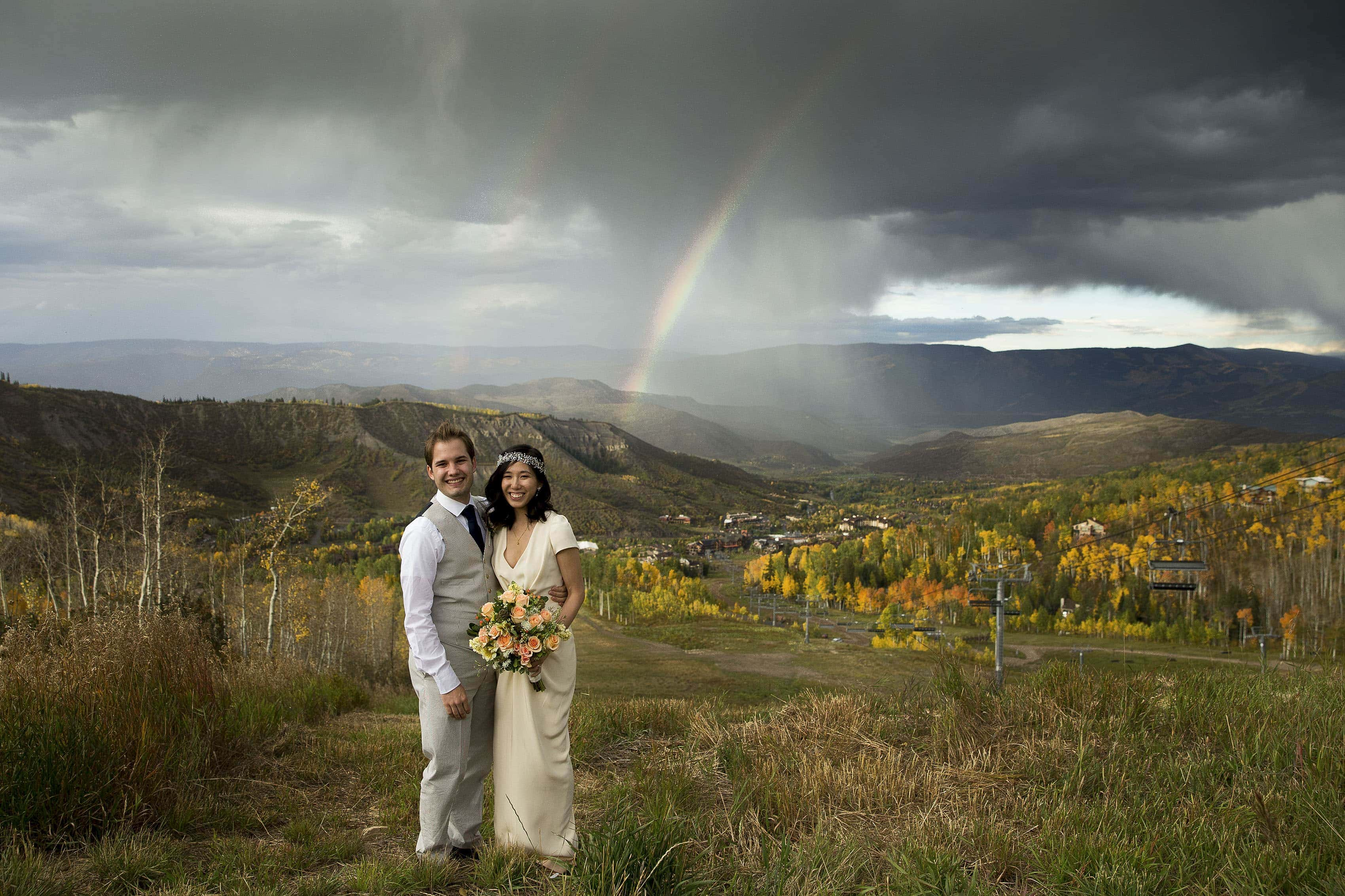 A couple pose as a rainbow illuminates the mountains surrounding Snowmass Village, Colorado during the fall