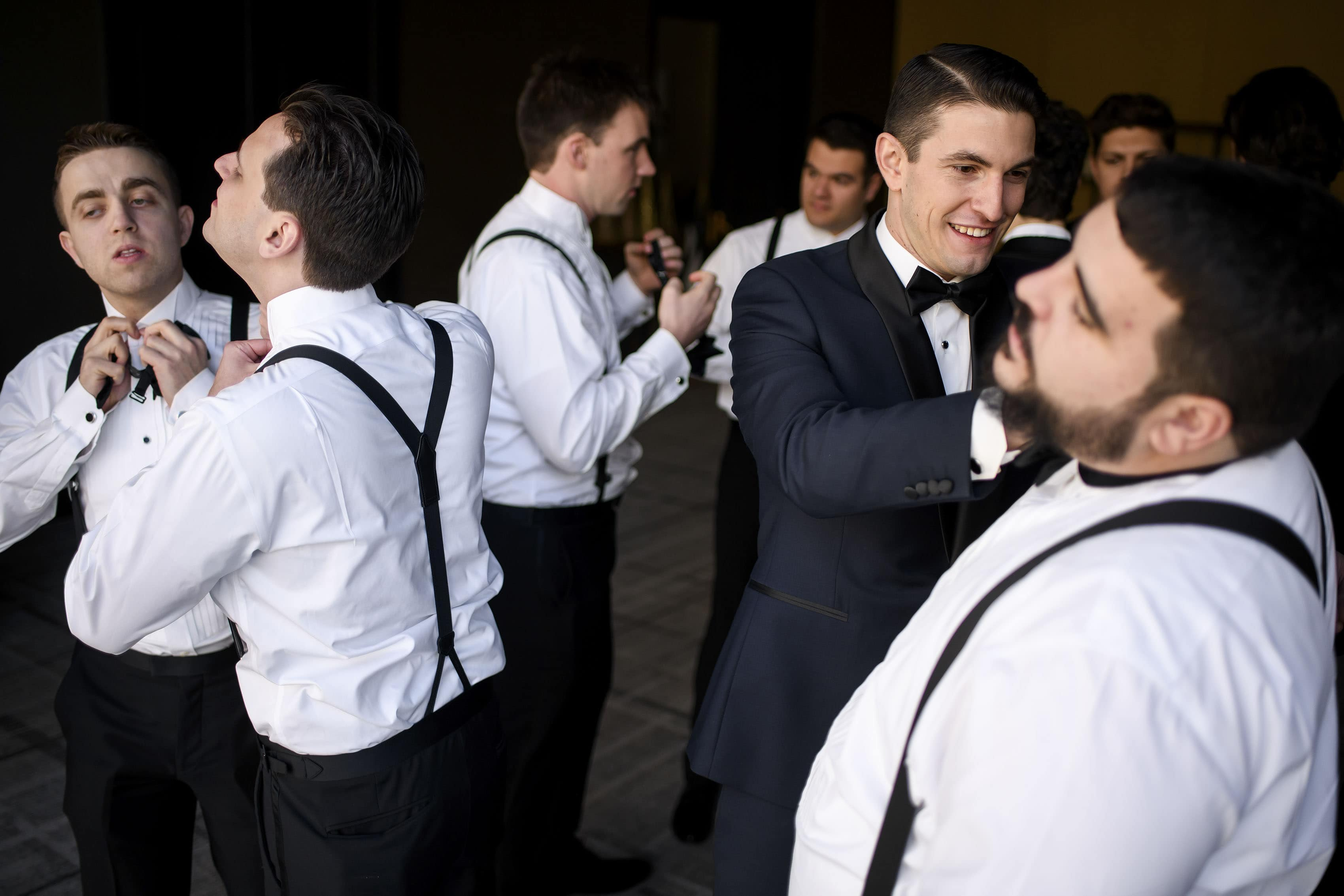 Alex helps a groomsment with his tie while getting ready for the wedding at the Halcyon Hotel in Denver