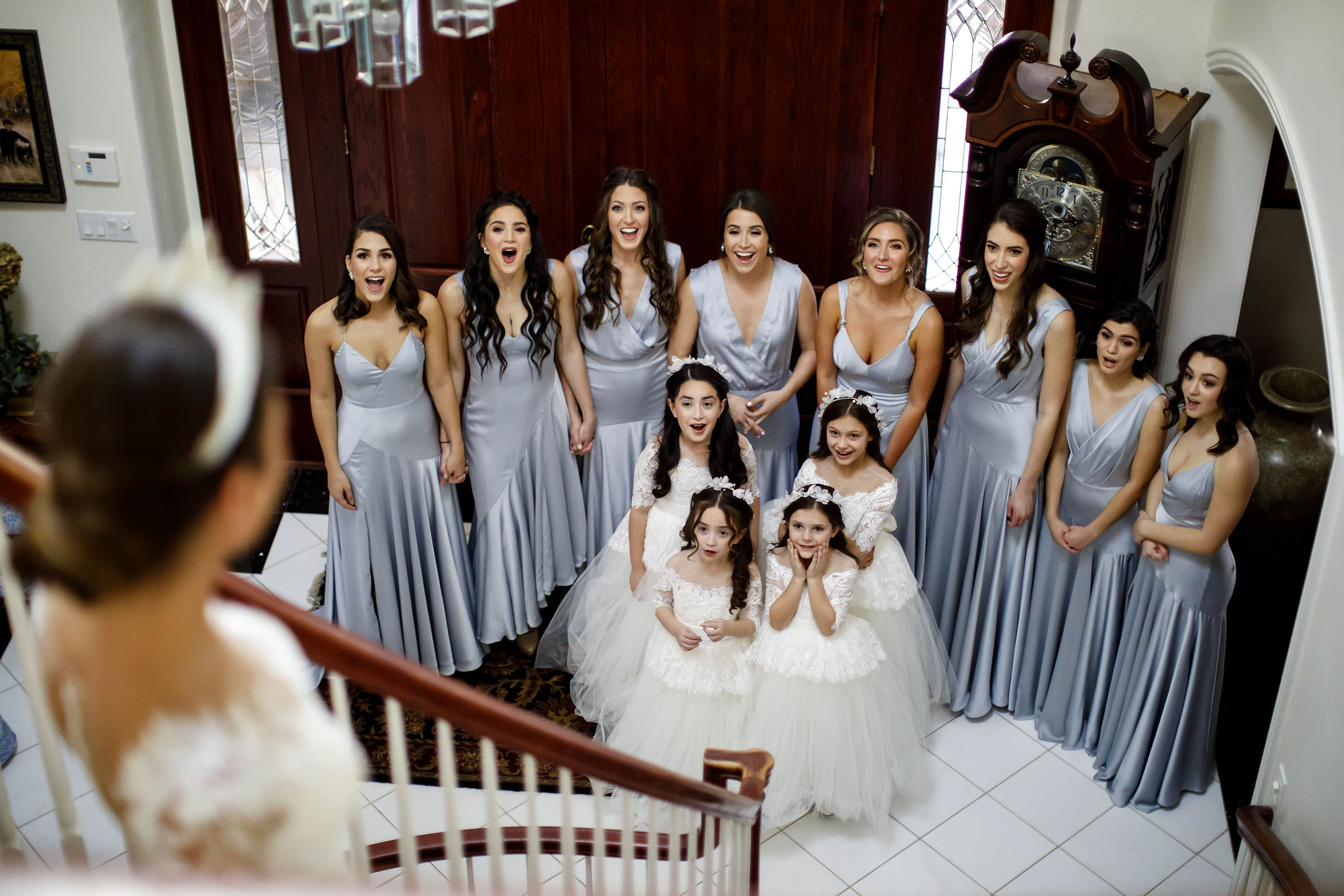 Ioanna's bridesmaids react as she walks down the grand staircase on her wedding day