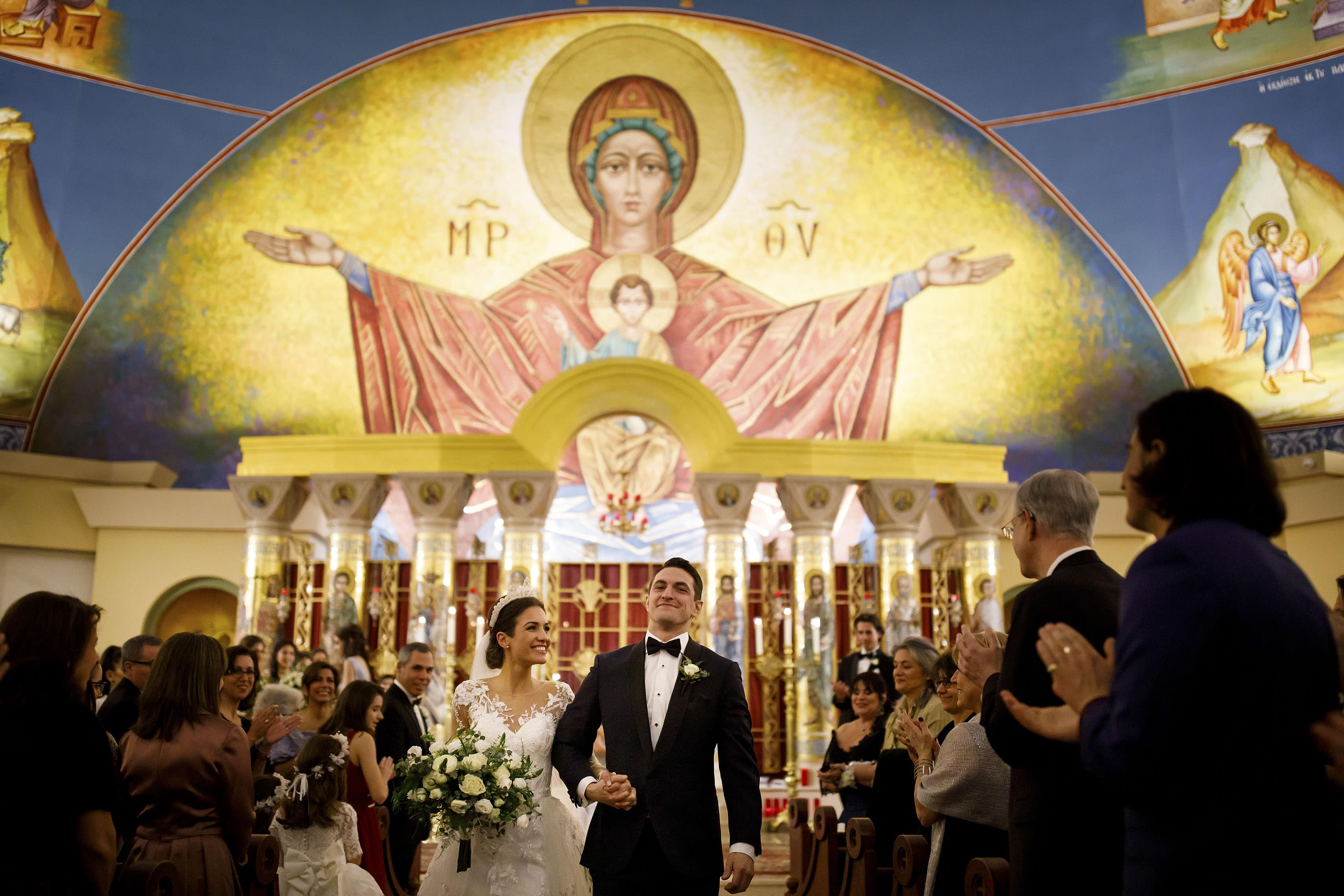 Ioanna and Alex walk down the aisle as a married couple following their colorful greek wedding in Denver at Assumption of the Theotokos Greek Orthodox Cathedral