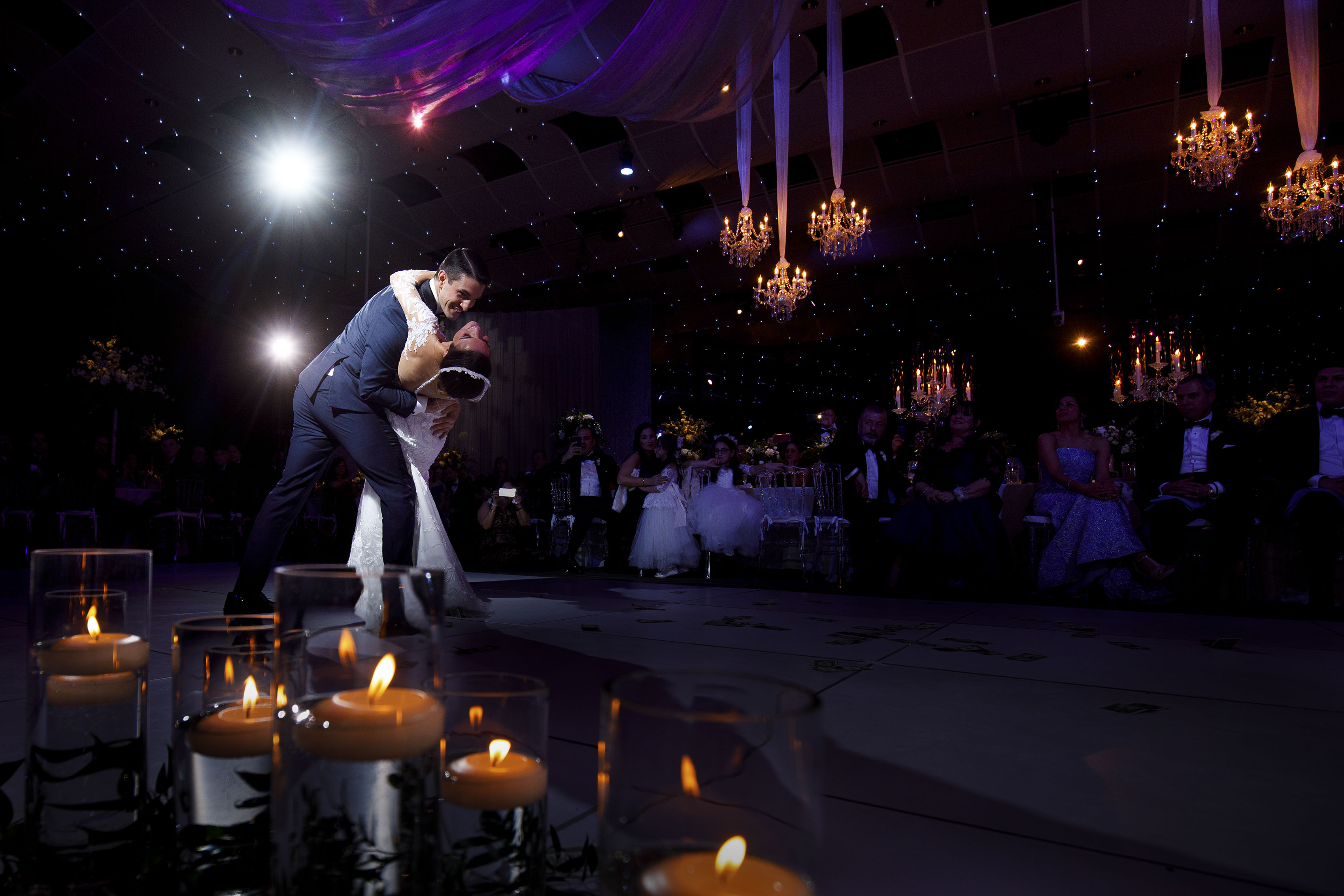 The groom dips the bride on the dance floor during their colorful greek wedding in Denver at Seawell Ballroom