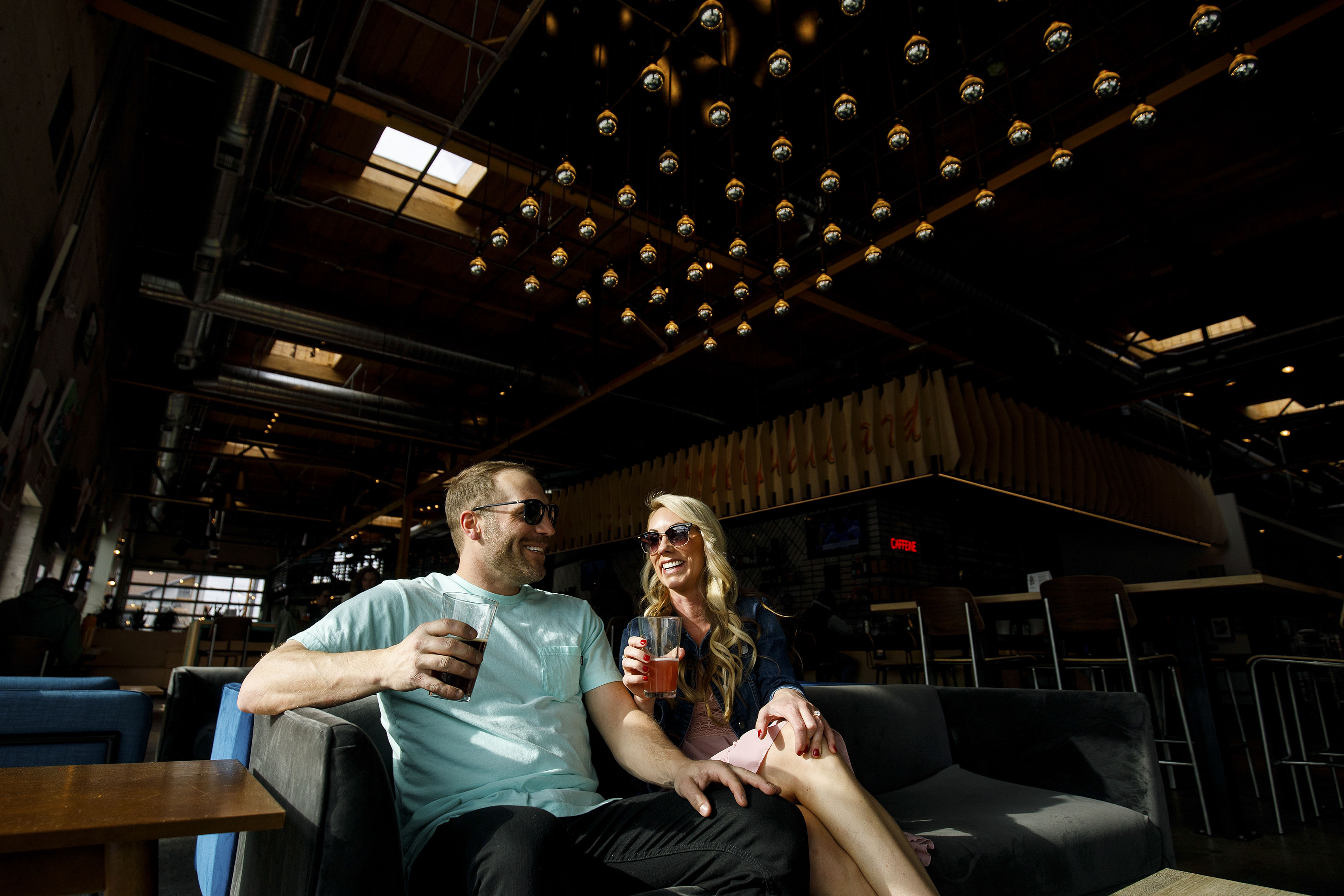 Mesha and Joe share a drink at Improper City in Denver during their engagement photos