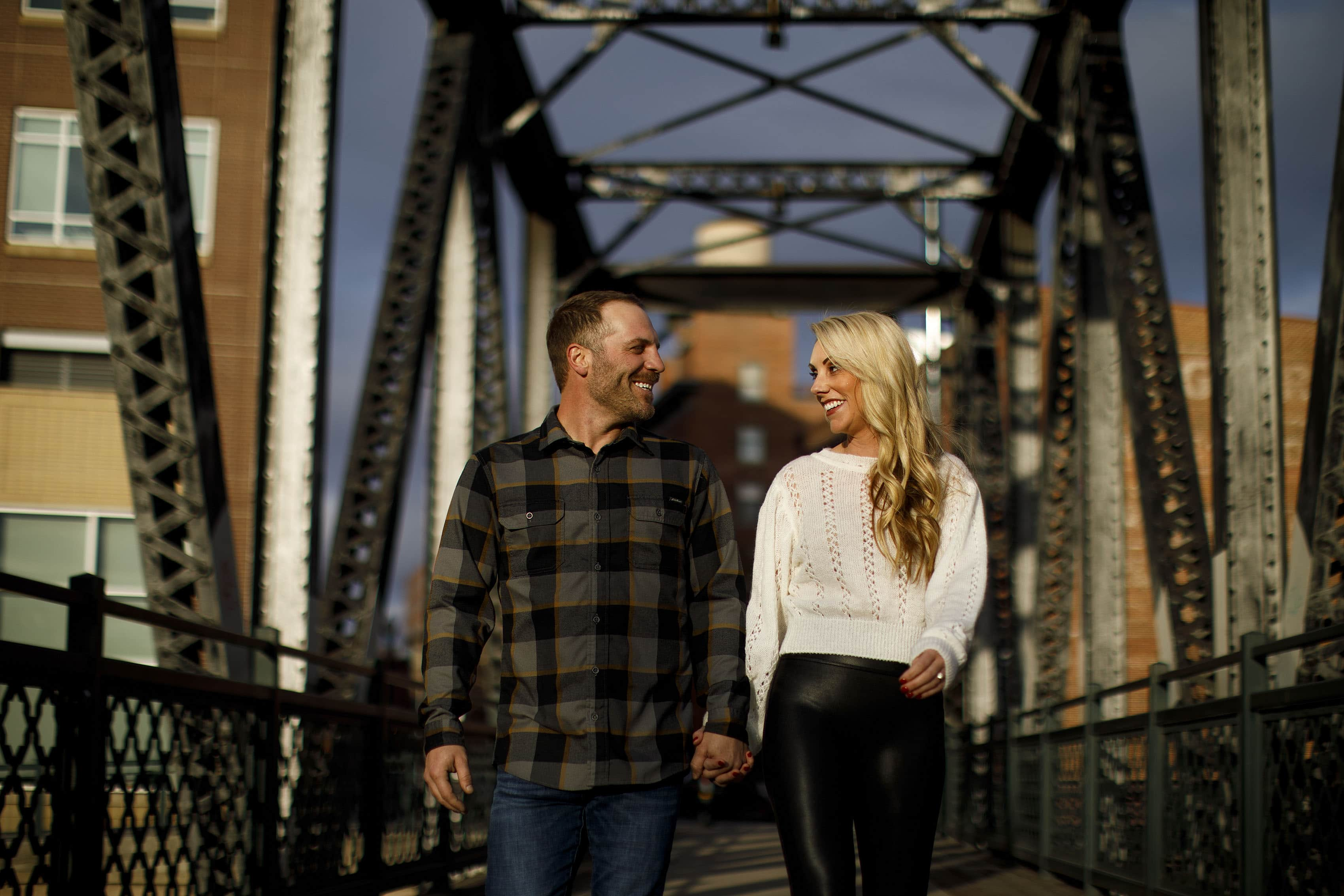 Joe and Mesha smile while walking together on the Wynkoop Street Bridge during their Denver engagement session