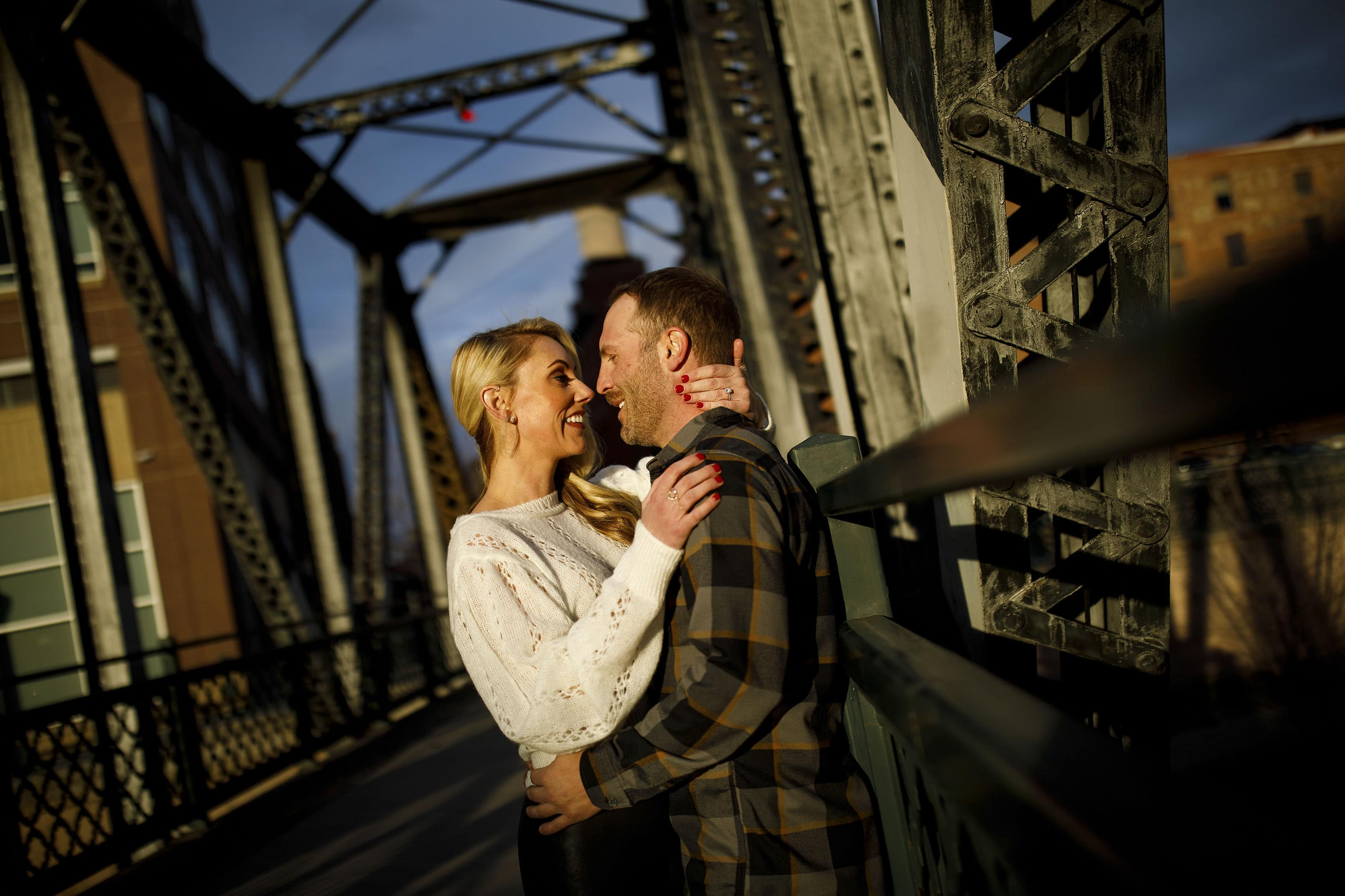 A couple share a moment together at sunset on the Wynkoop Street Bridge during their engagement photos in downtown Denver