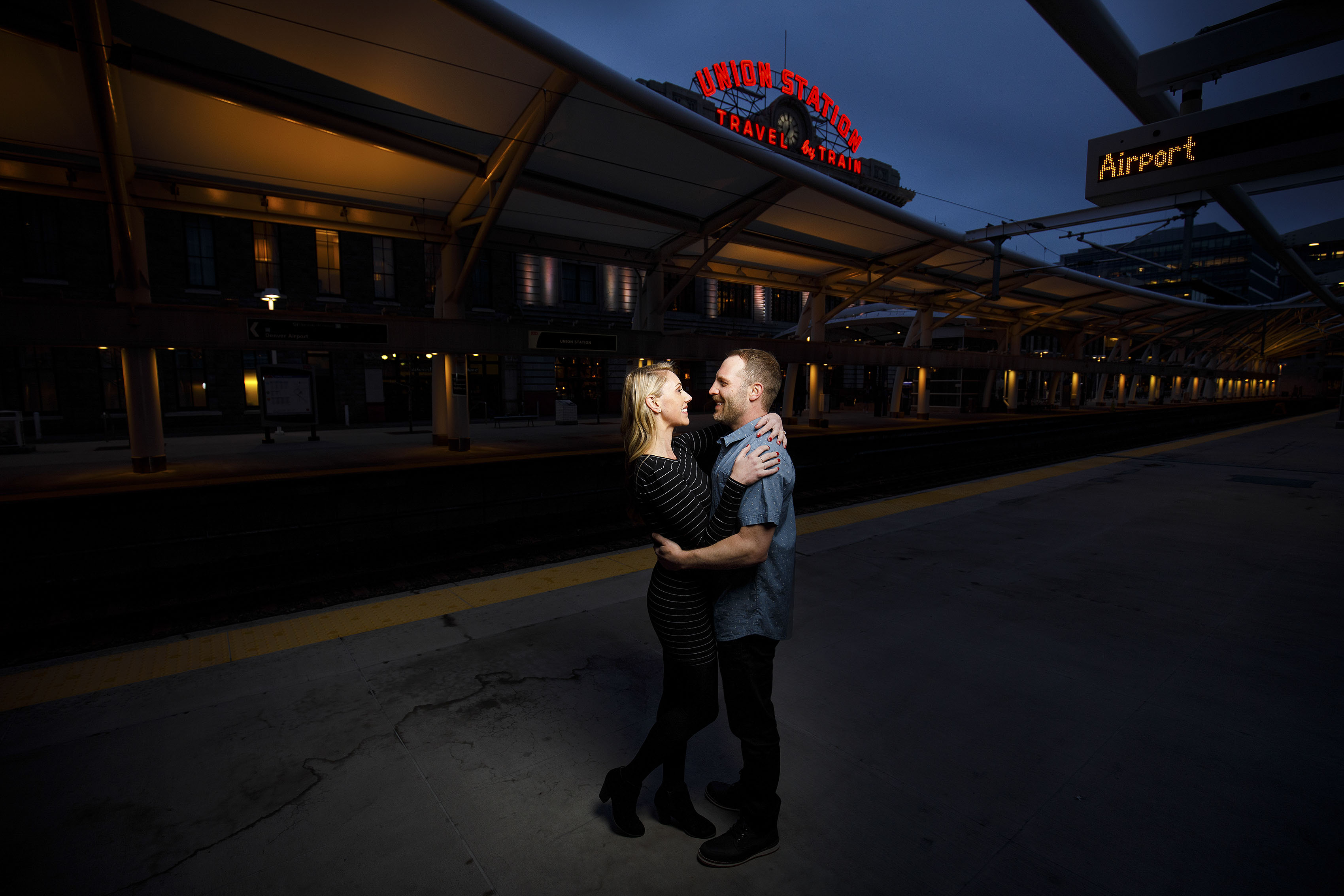 A couple poses on the train platform at Denver's Union Station during their engagement photos