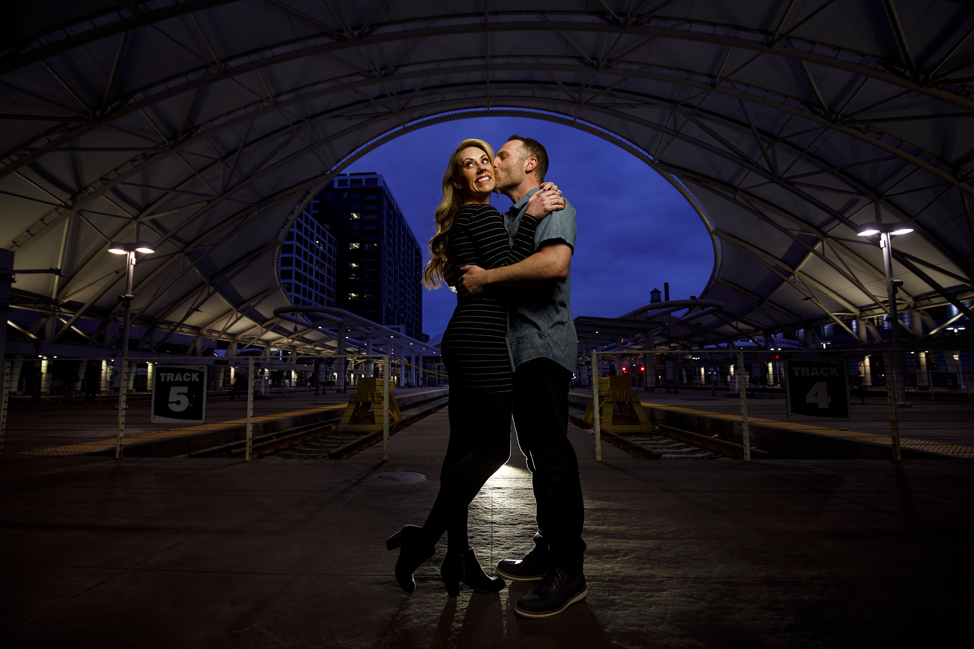 Joe kisses Mesha near the train platform at Union Station Denver during their engagement photos