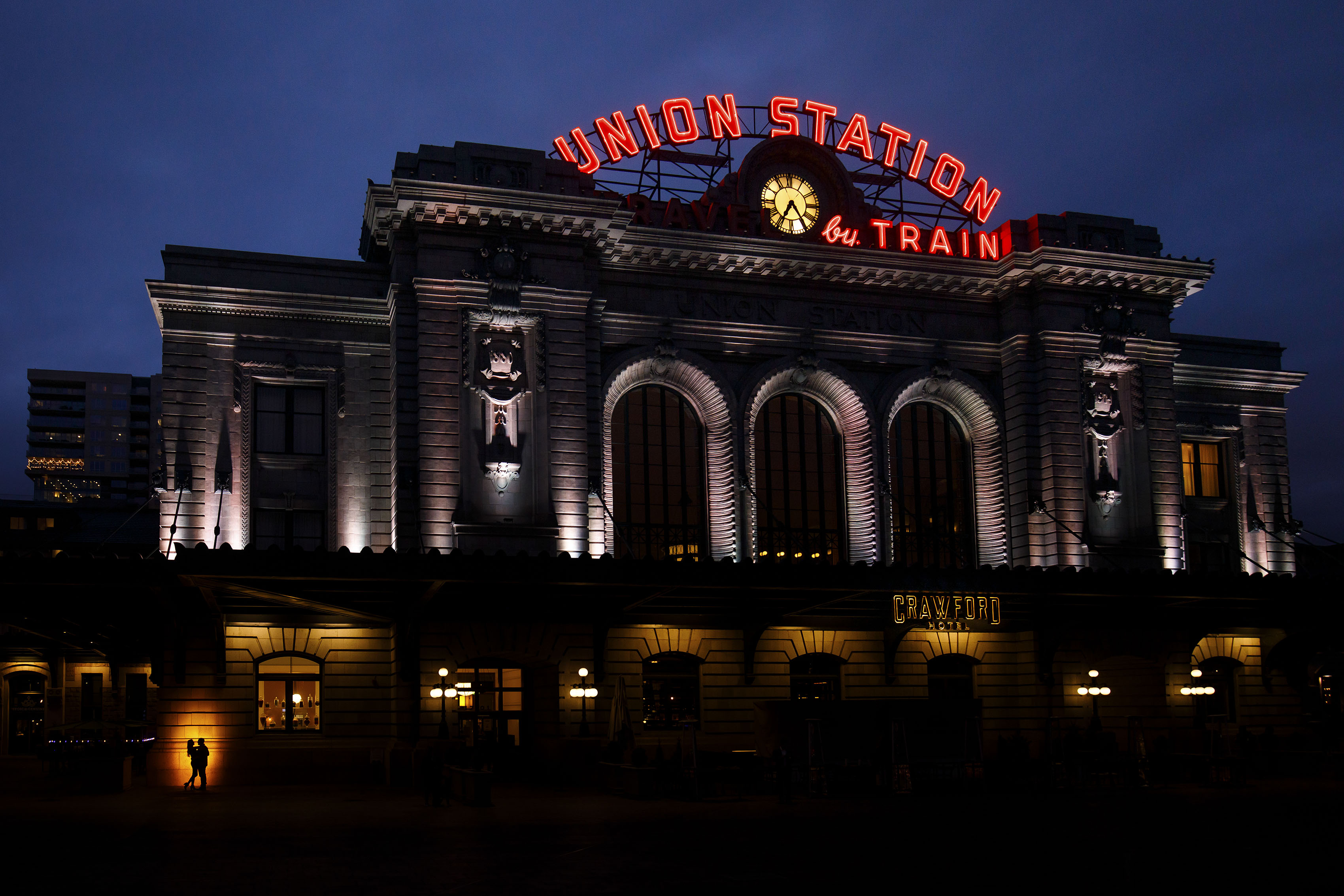A couple is silhouetted against the building at Denver's Union Station during their engagement photos in lower downtown