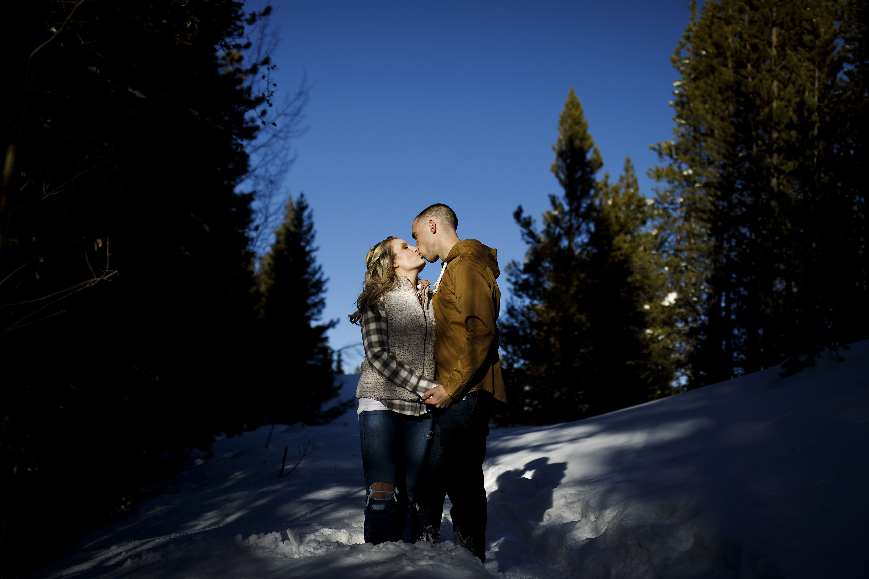 Shane kisses Cassidy in the snow during their engagement session in Breckenridge