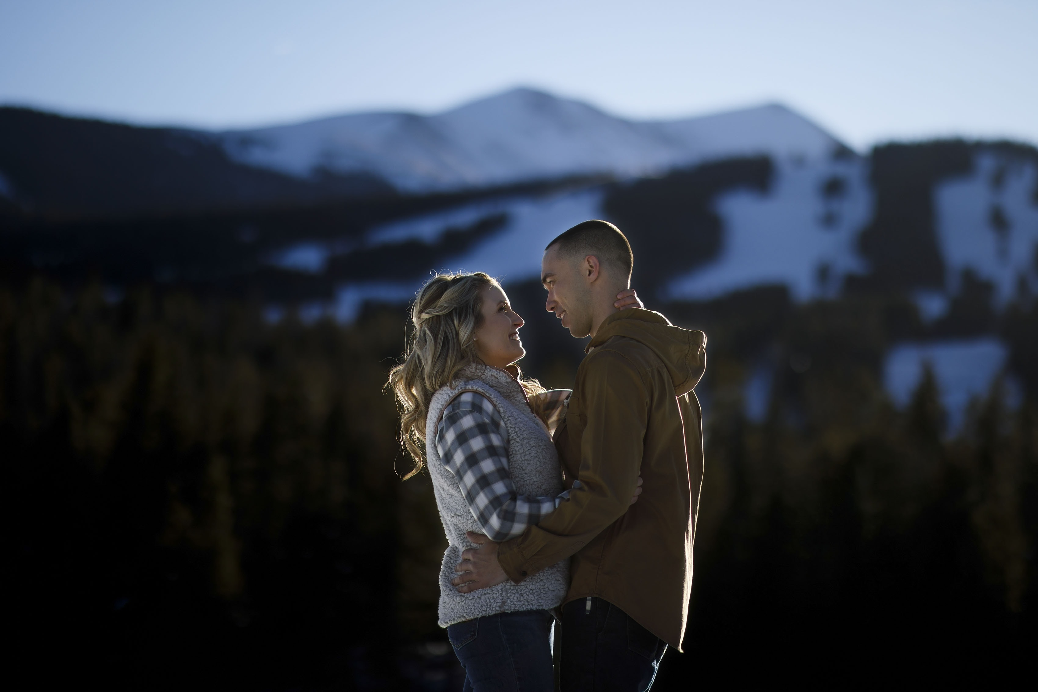 Cassidy smiles at Shane near Breckenridge resort during their winter engagement session