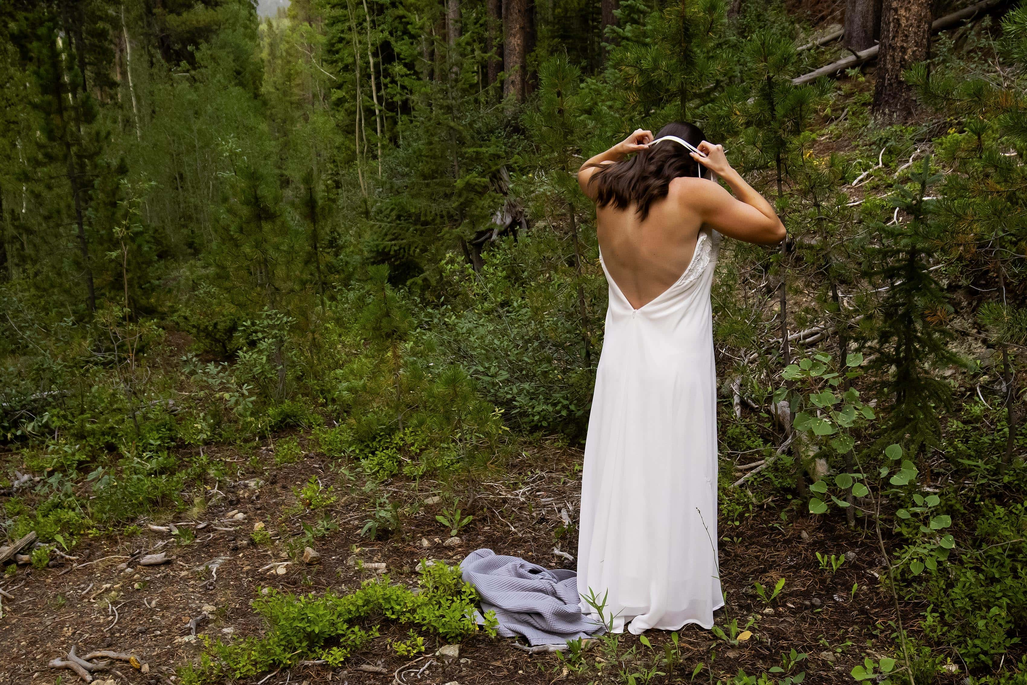 Marla puts her dress on in the woods before her elopement