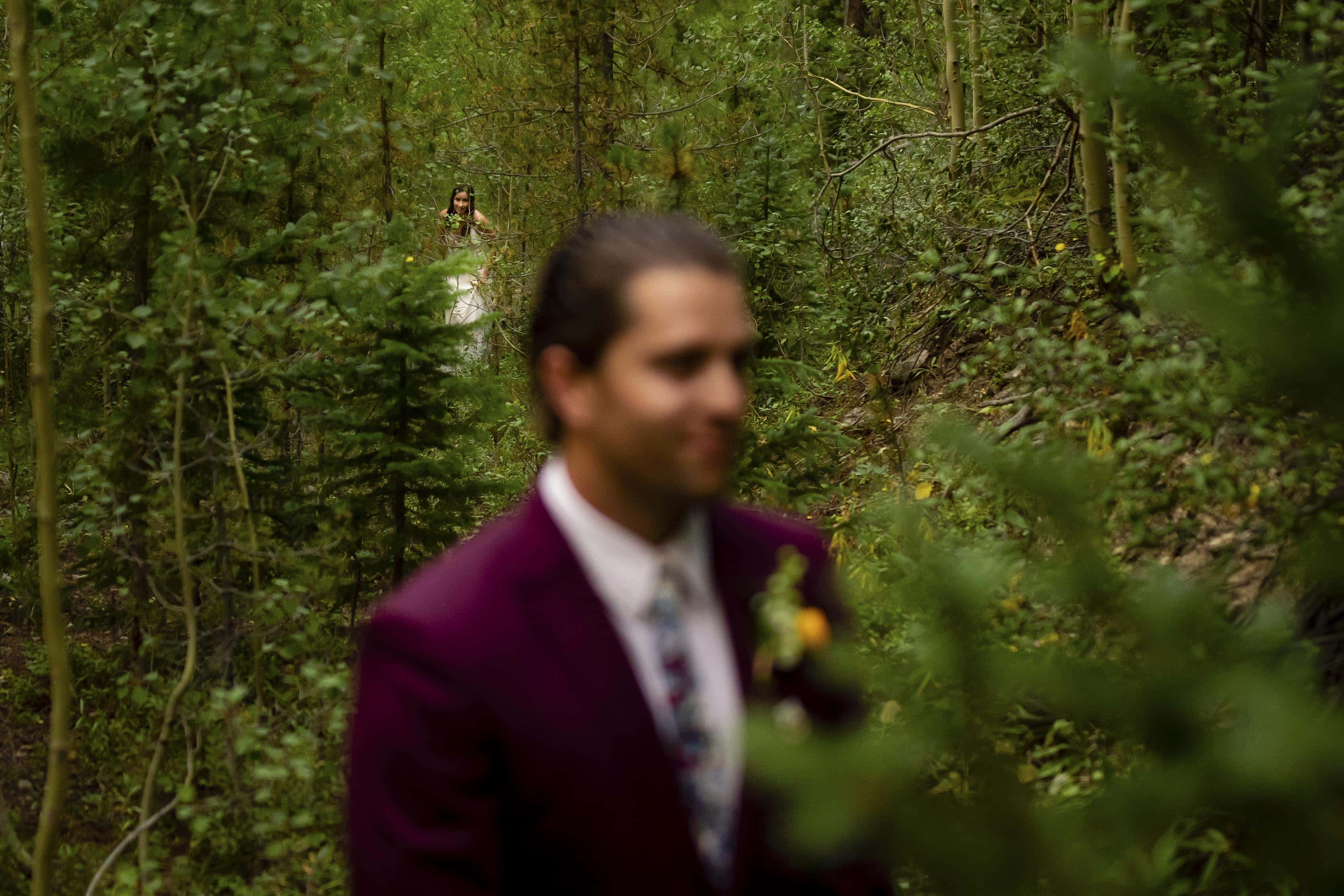 The bride sneaks through the trees before the coupleÕs first look on their wedding day
