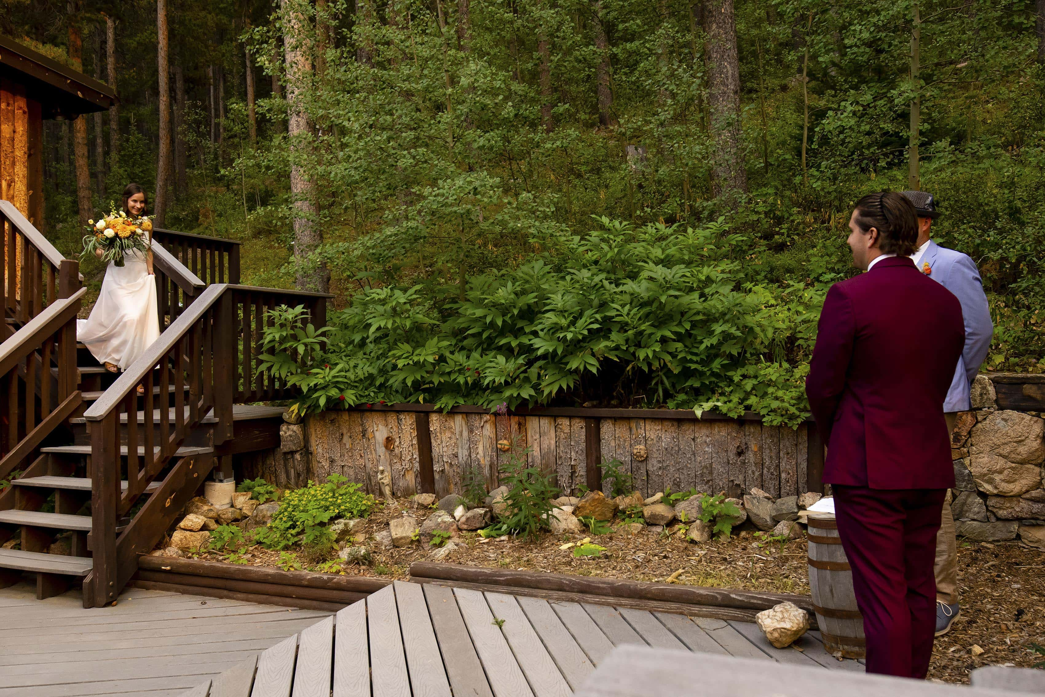 The bride walks down the stairs during the mountain house elopement