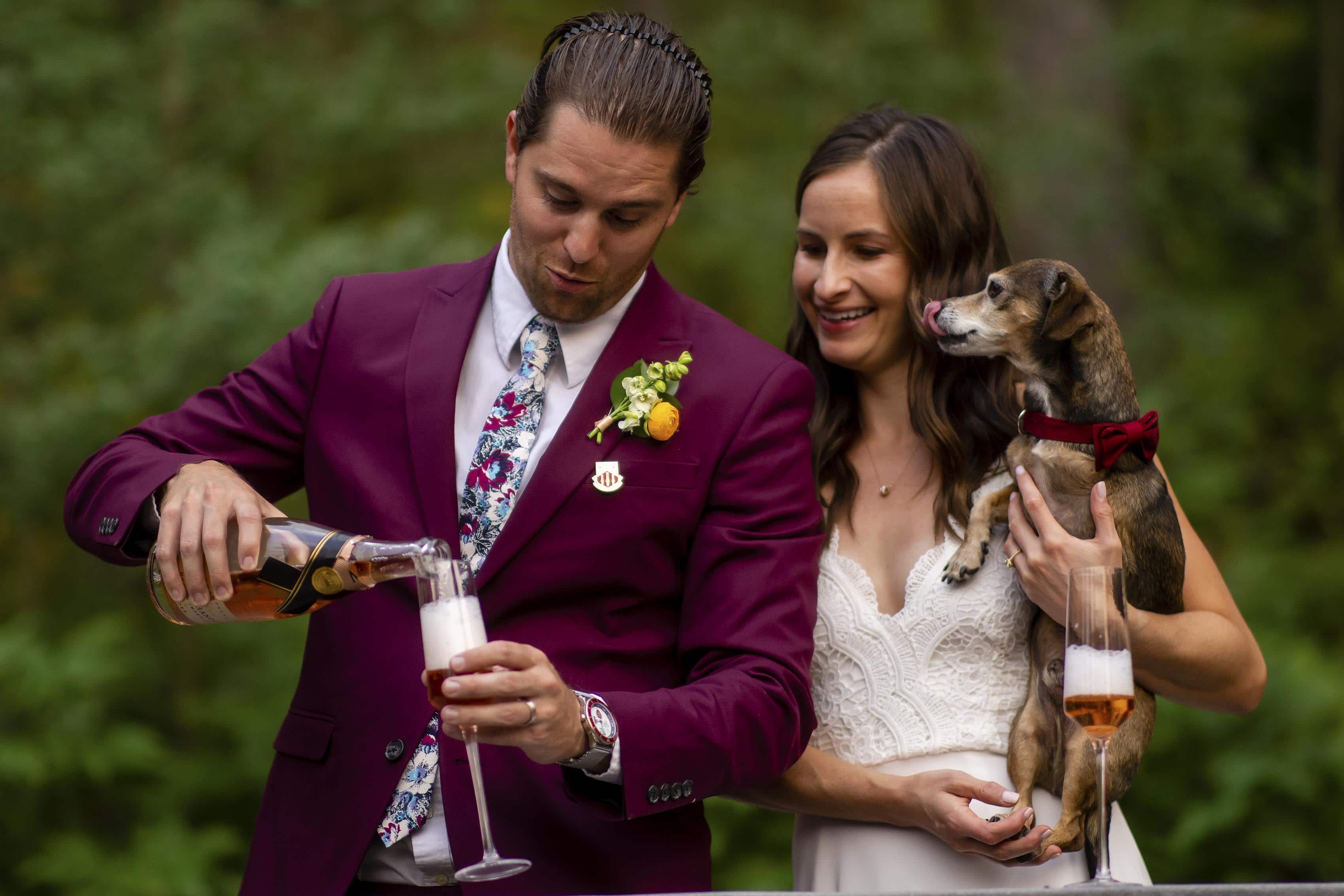 The groom pours champagne as bride holds their dog after their elopement ceremony in the mountains of Colorado