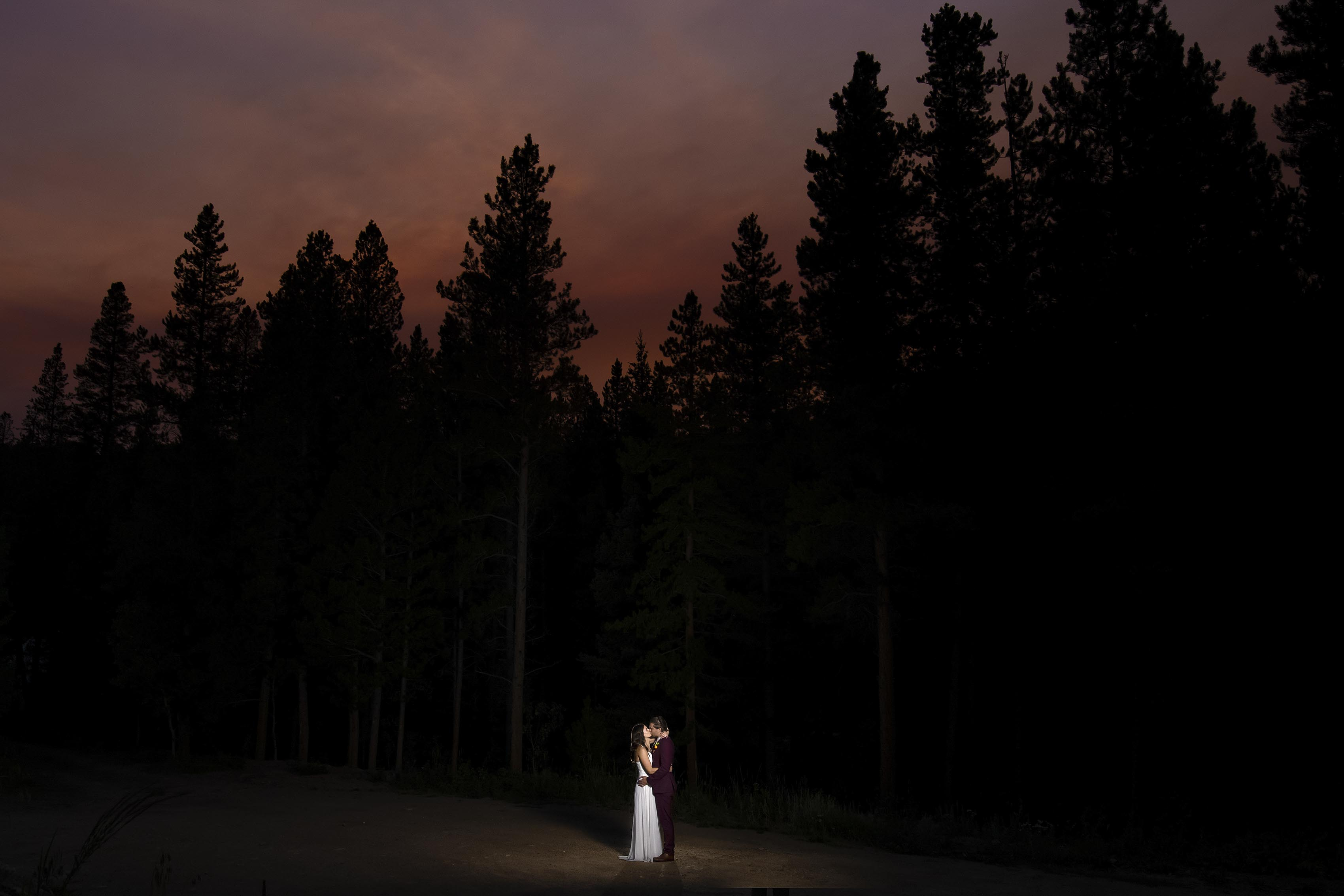 The newlyweds share a kiss under a smoky sunset following their elopement in Black Hawk, CO