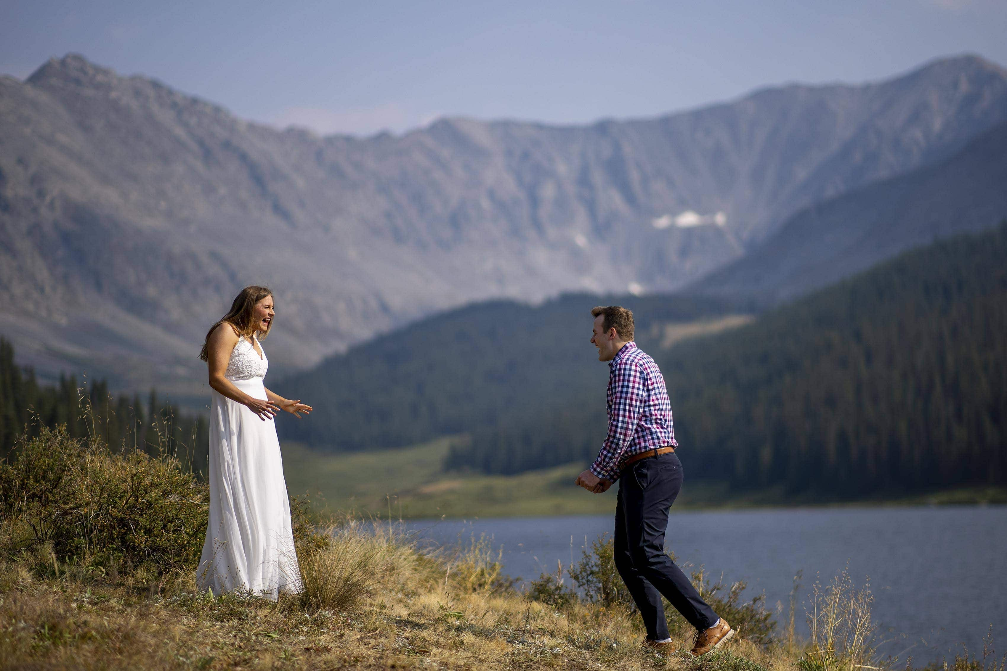 Mel and Drew react during their first look at Clinton Gulch Dam Reservoir during their wedding