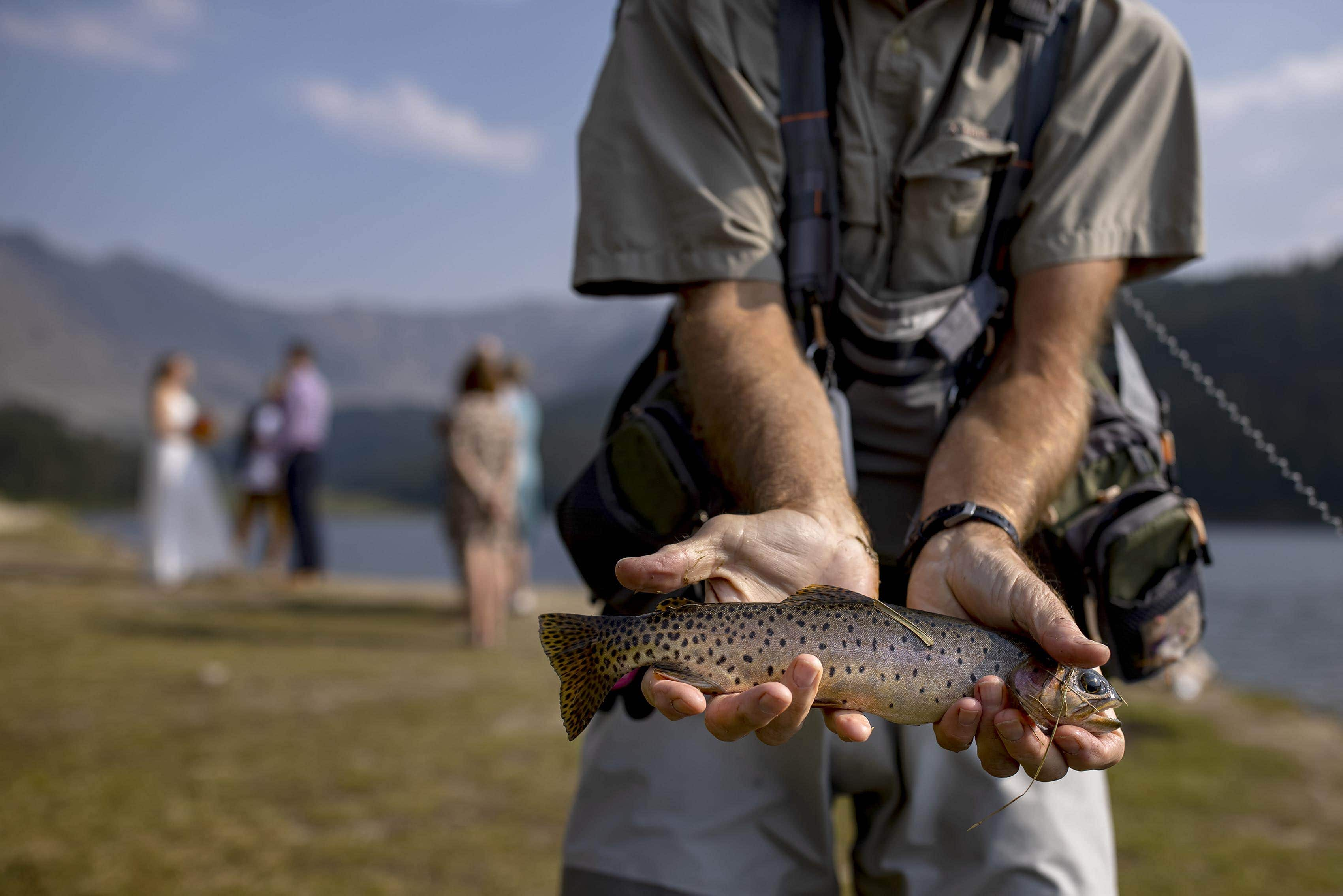 A fisherman holds up a trout near a wedding ceremony