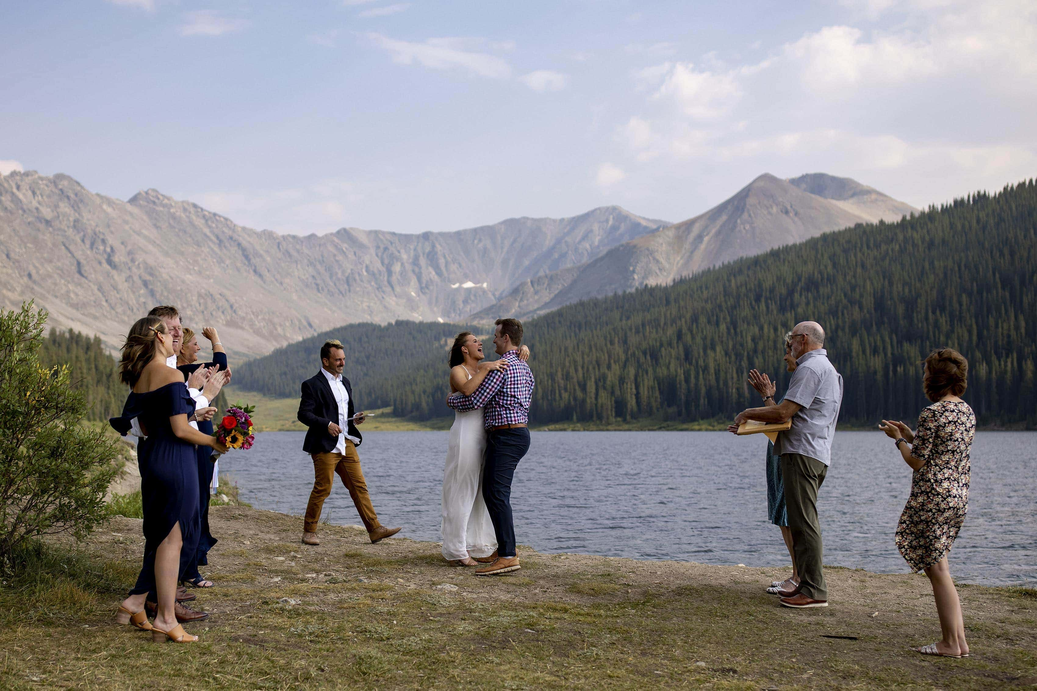 The couple react during their wedding ceremony at Clinton Gulch Dam Reservoir