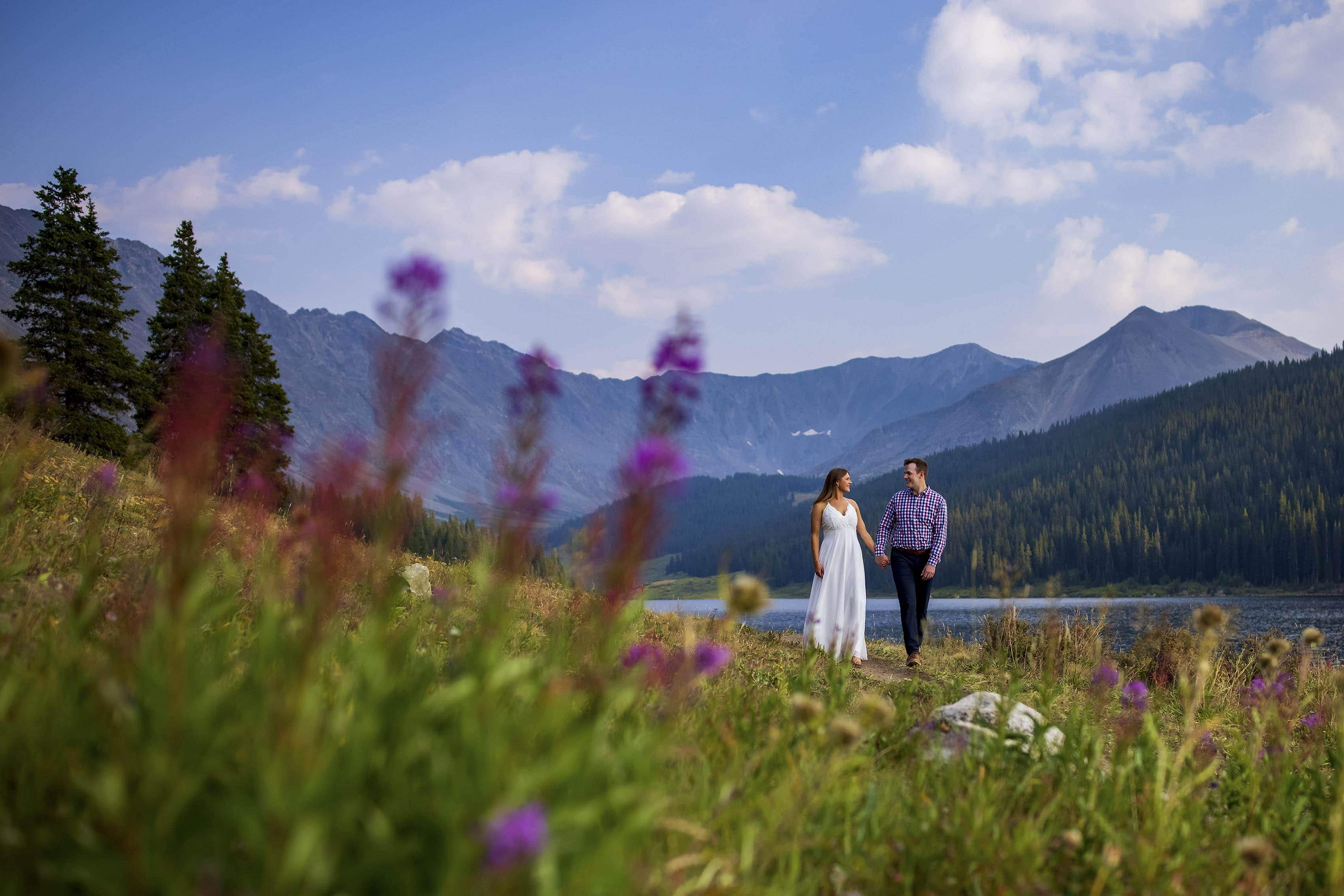 Wildflowers in bloom as a bride and groom walk together at Clinton Gulch Dam Reservoir