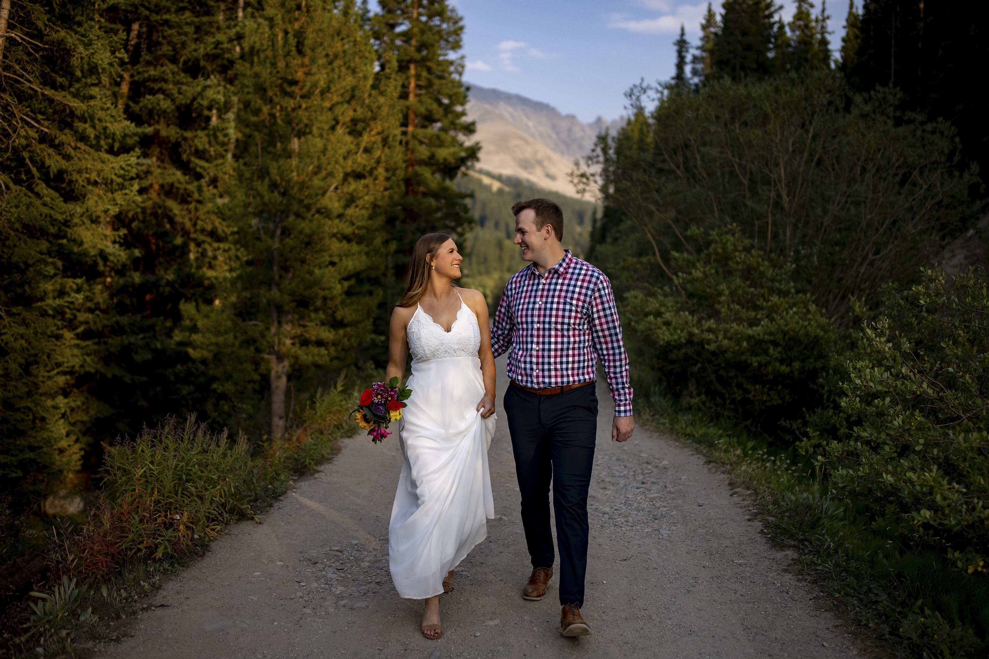 Mel and Drew walk together on the path at Mayflower Gulch in Colorado on their wedding day