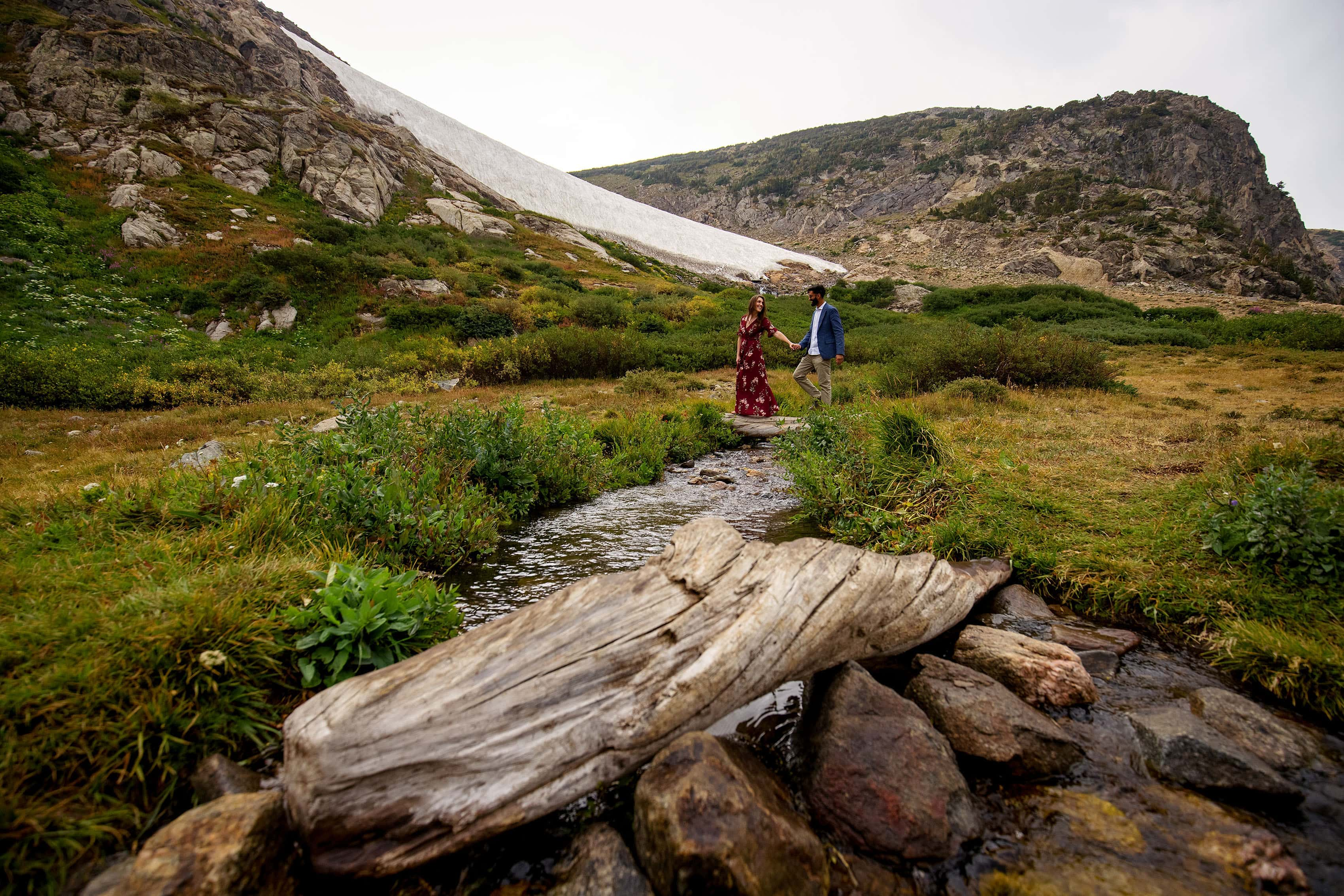A couple walk across the stream at St. Mary's Glacier