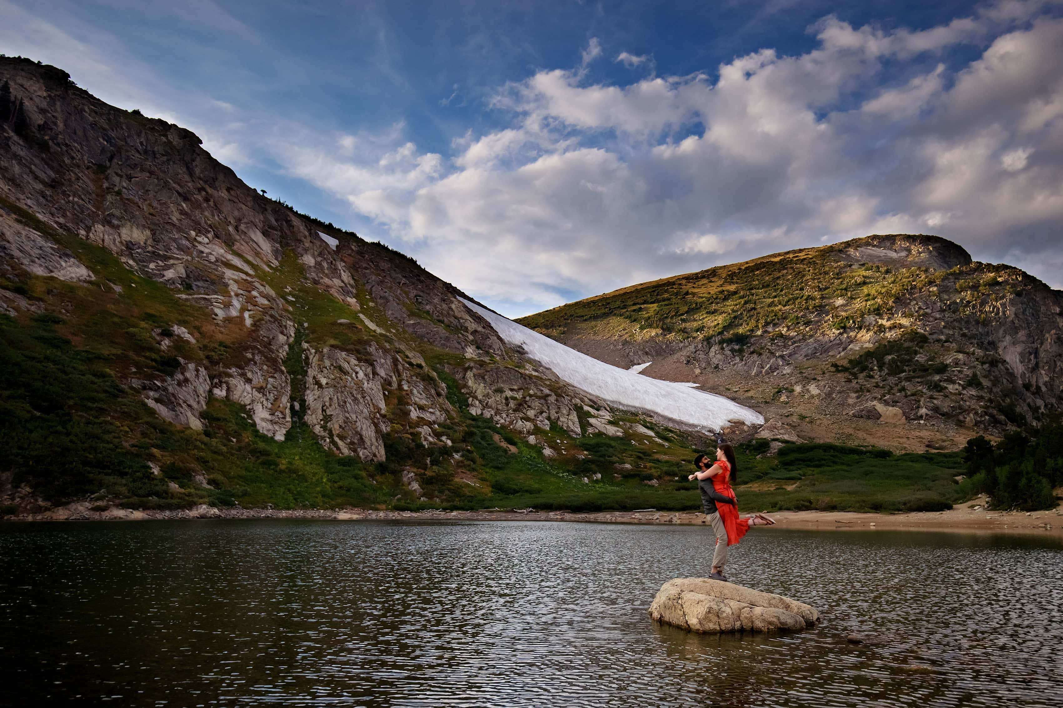 Moypa picks up Kara on a rock in the pond at St. Mary's Glacier during their engagement session