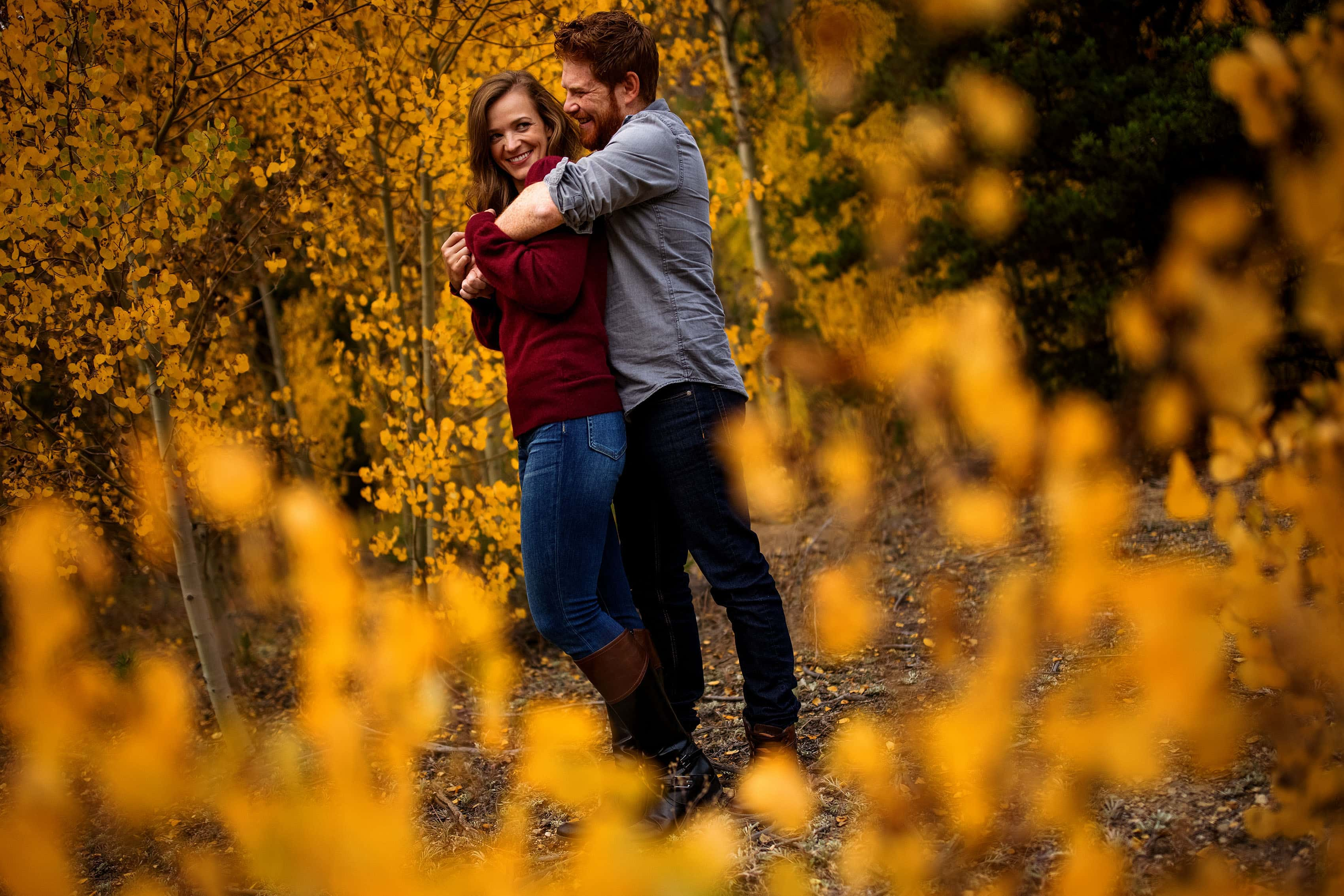 A couple poses in a grove of colorful aspen trees