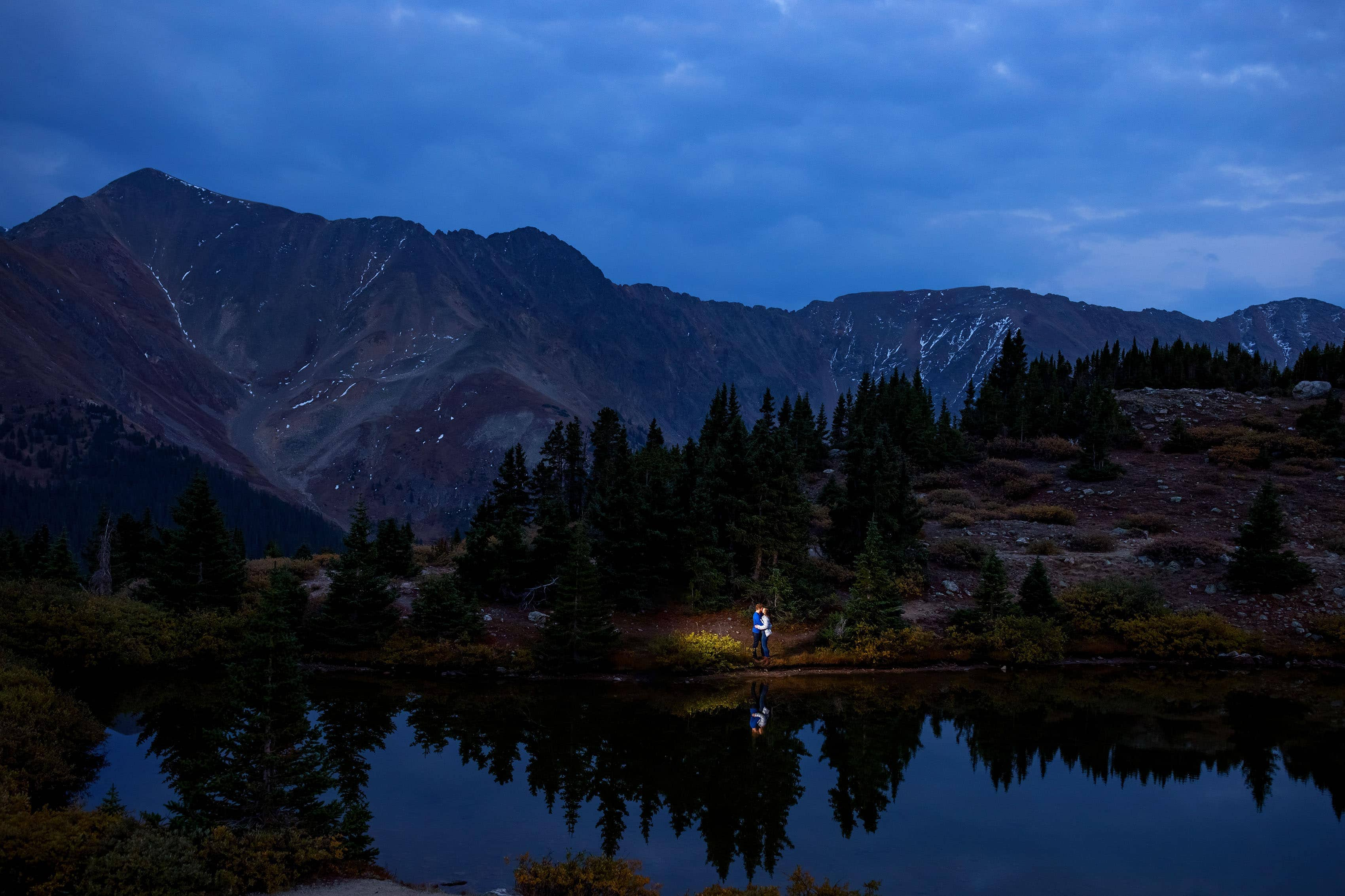 A couple share a kiss next to a high mountain lake at twilight during their engagement session near Loveland Pass