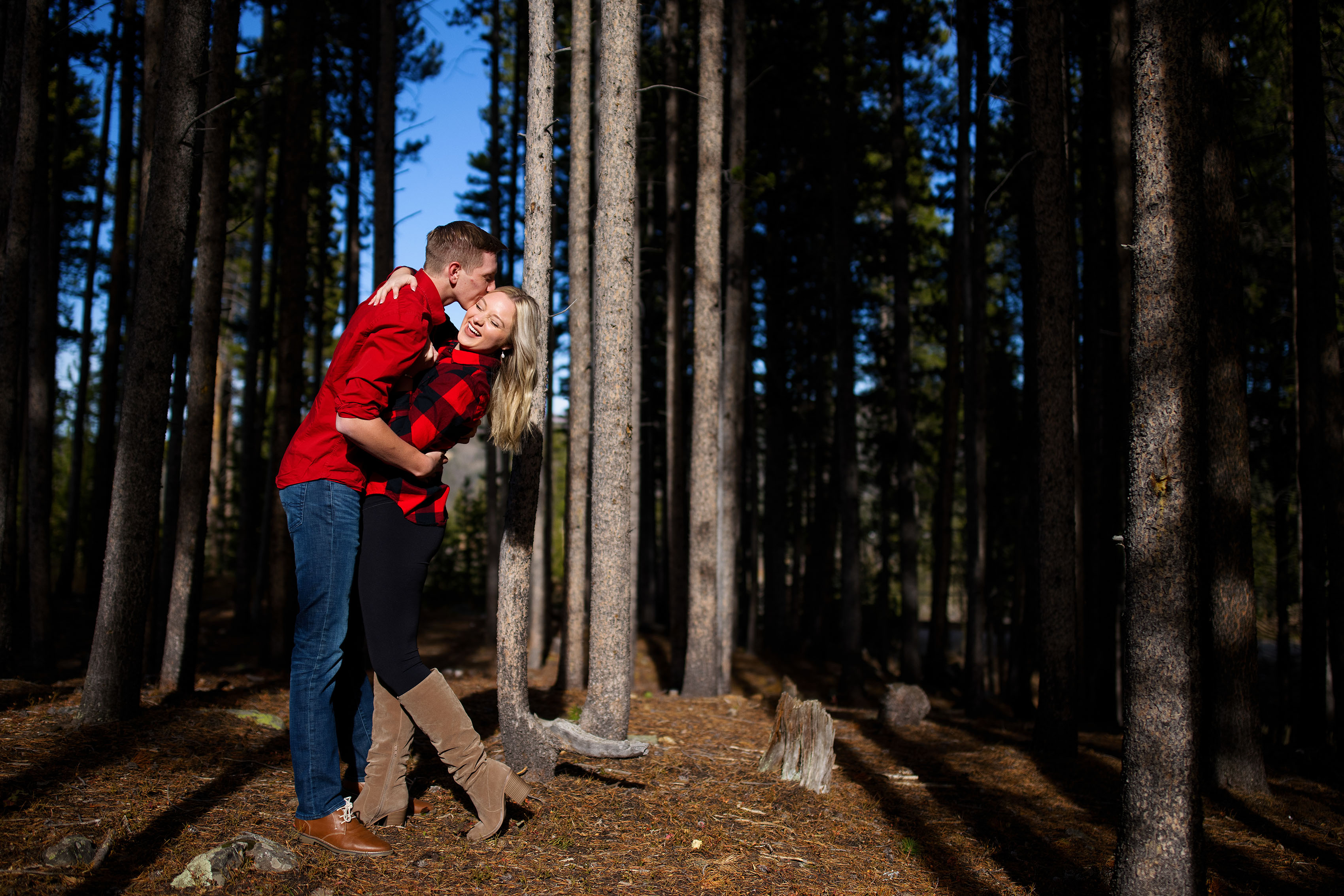 Joseph kisses Chloe in a grove of pine trees at Sawmill Reservoir