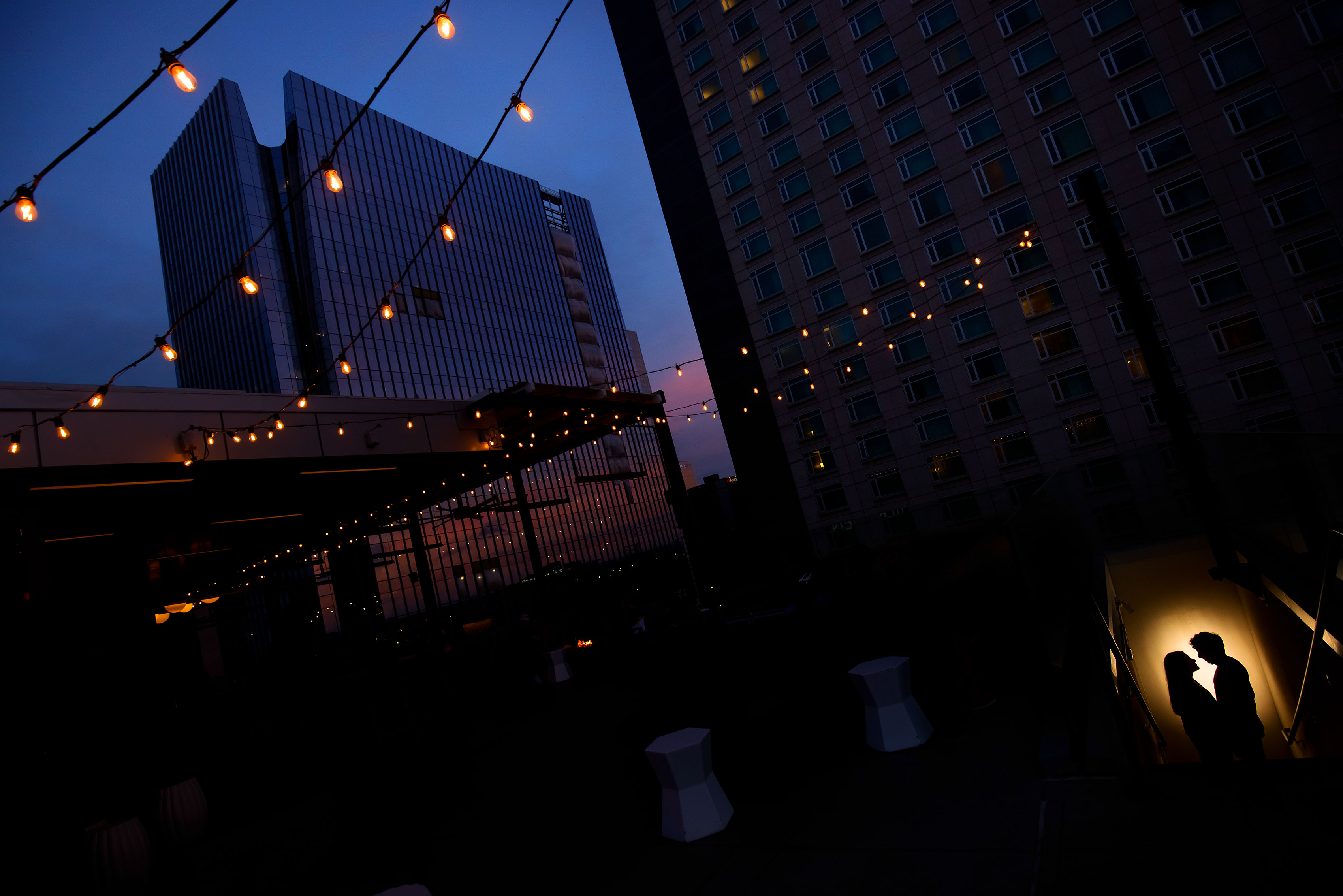 A couple is silhouetted under the market lights at sunset on top at 54thirty rooftop bar in Denver