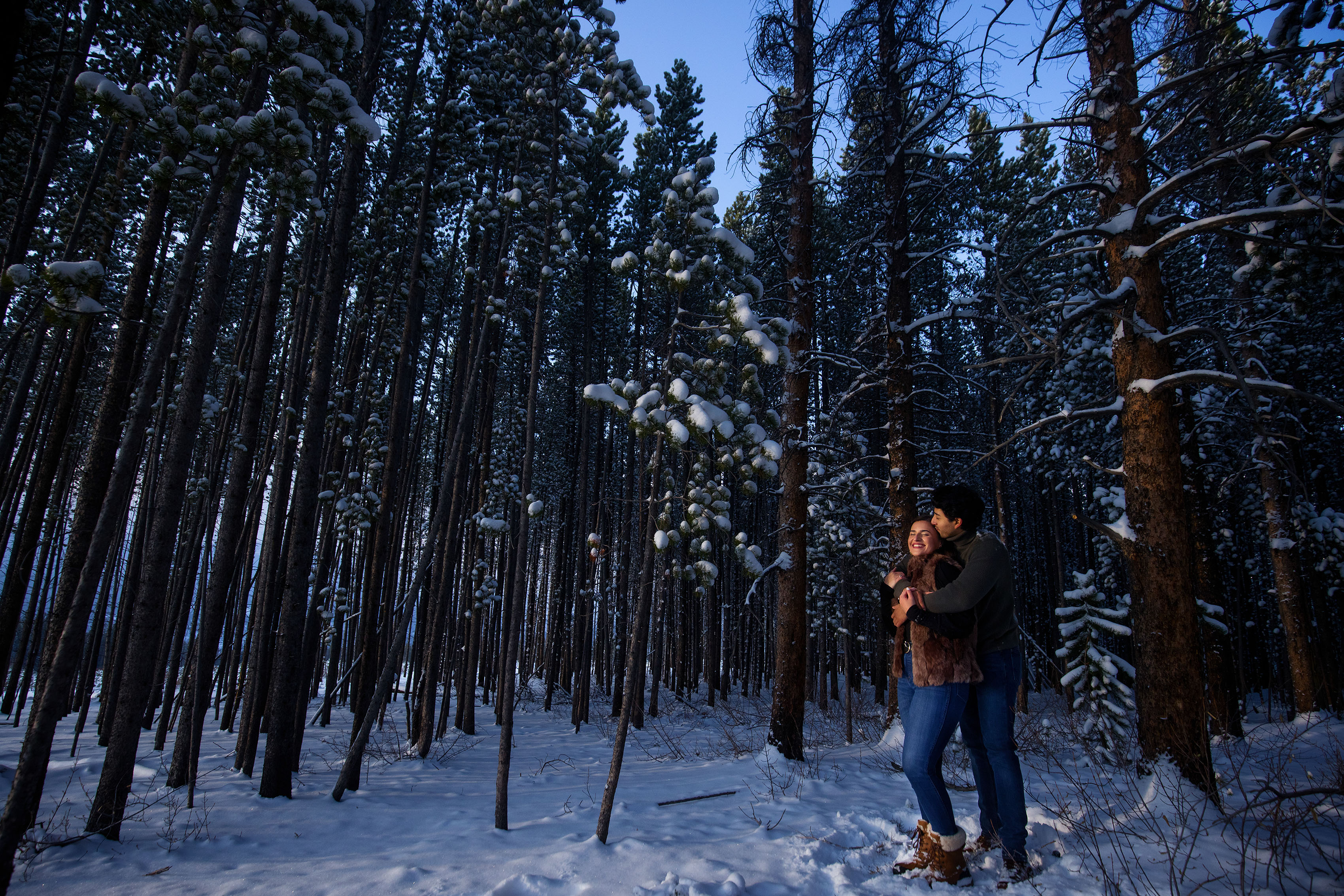Raul kisses Kooper while standing in a grove of snowy pine trees in Breckenridge