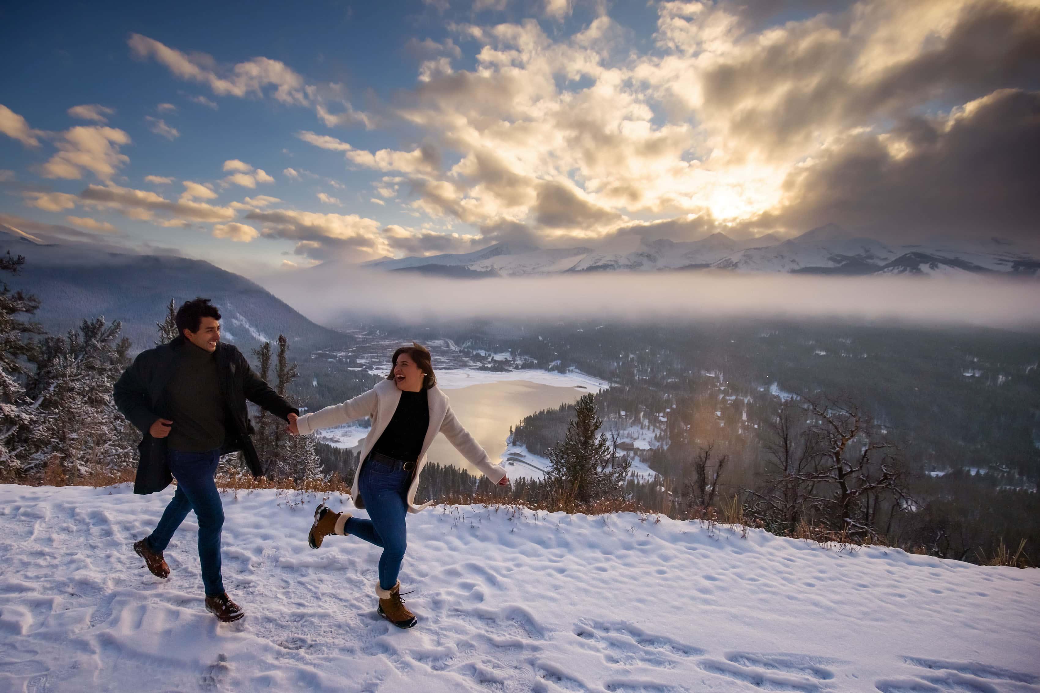 A couple runs along Boreas Pass Road in the snow as the snow sets behind BreckenridgeÕs Ten Mile Range during their engagement photos