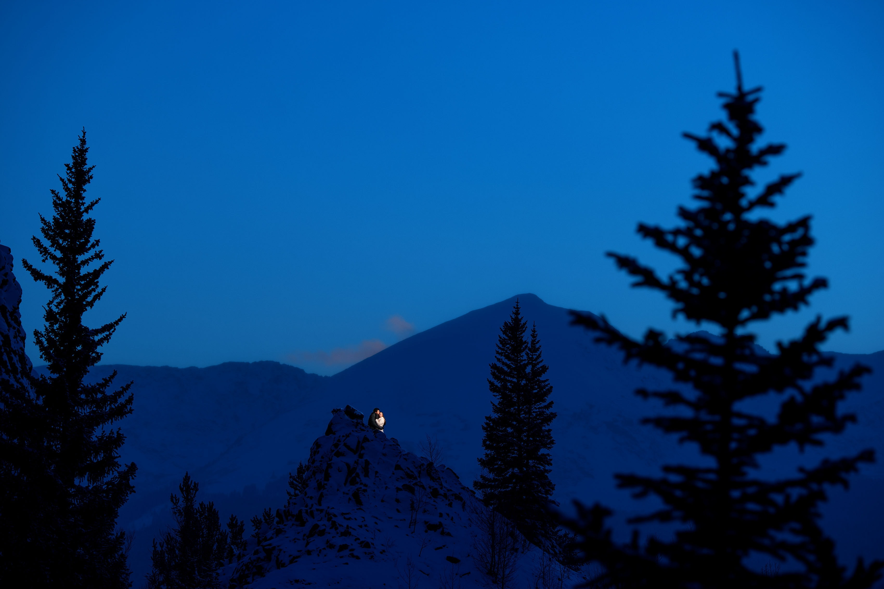 A couple share a moment at twilight atop Rocky Point on Boreas Pass Road during their winter wonderland engagement photos