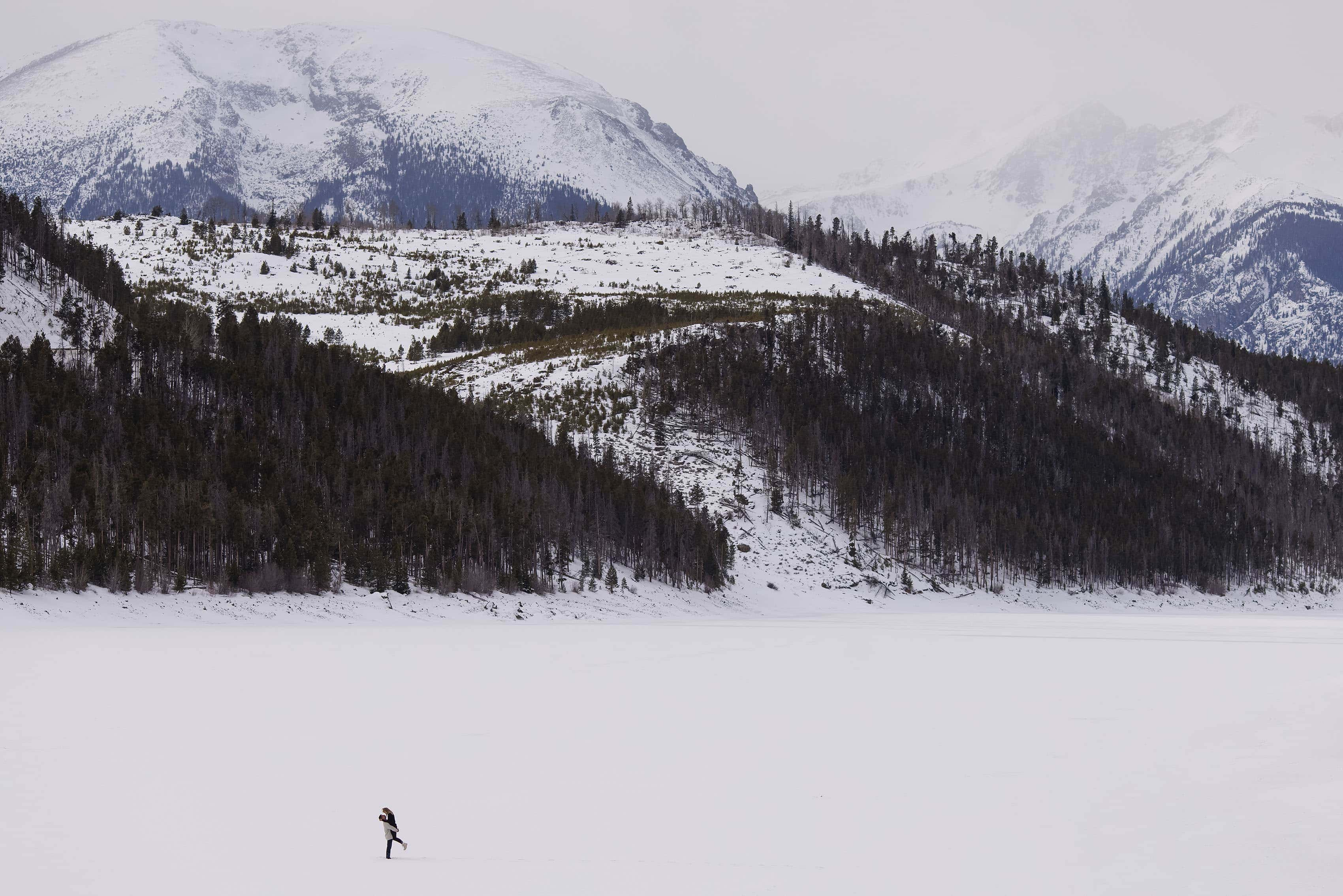 A couple embraces on Lake Dillon in the snow near the Tenmile Range