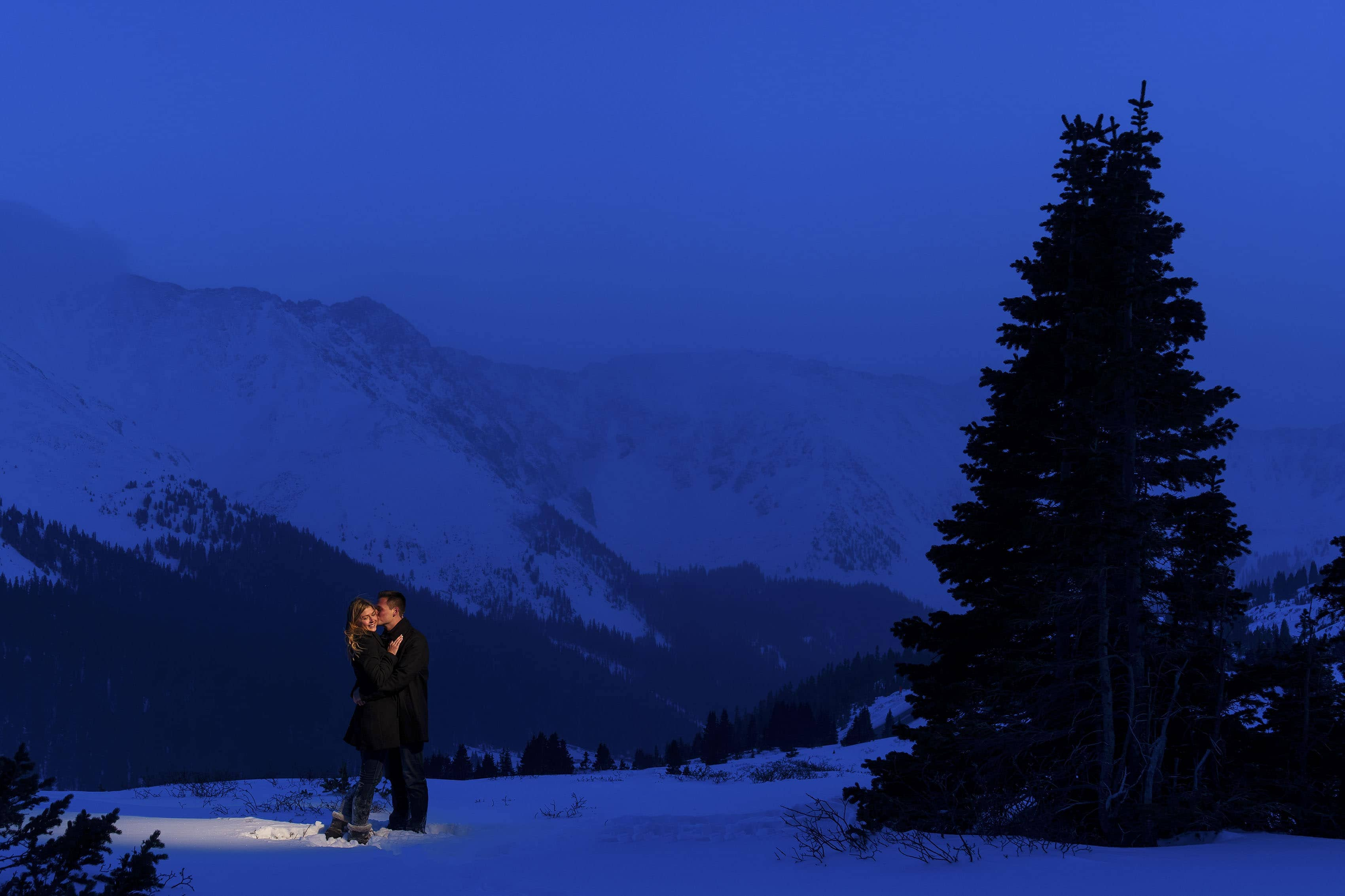 Scott kisses Kayla at twilight atop Loveland Pass during their engagement session