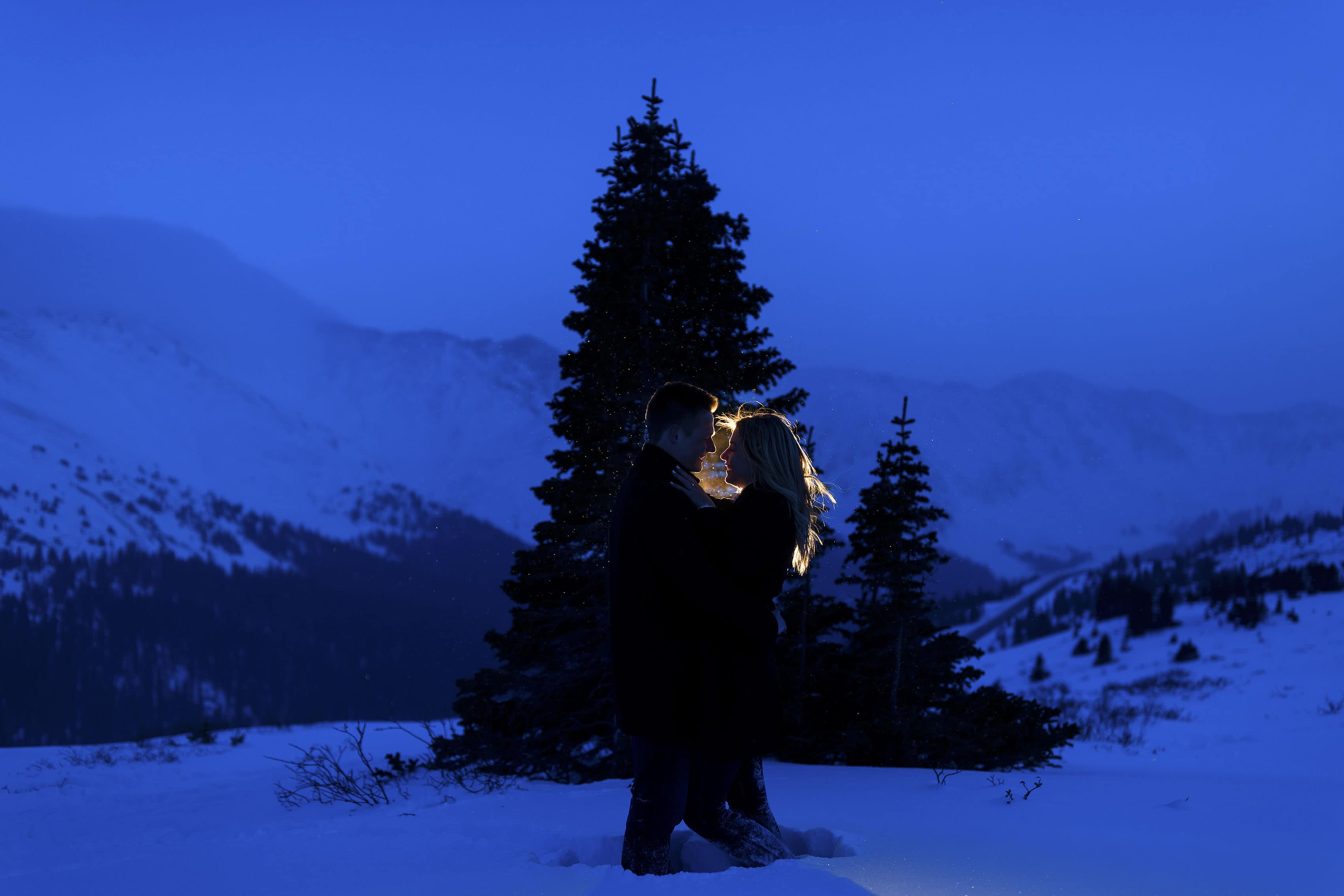 A couple is illuminated on Loveland Pass during their engagement photos