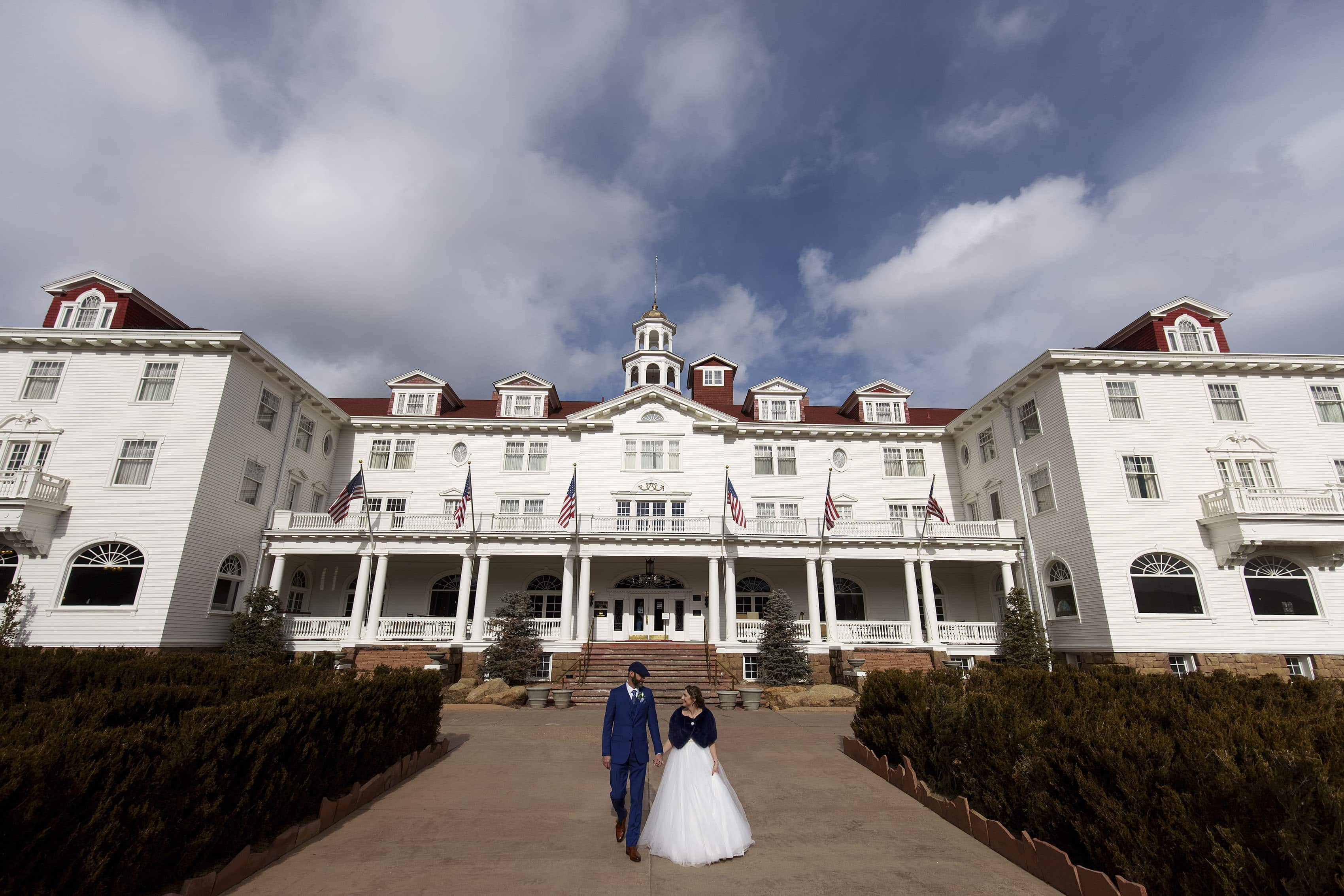 Newlyweds walk together outside of The Stanley Hotel in Estes Park during their elopement