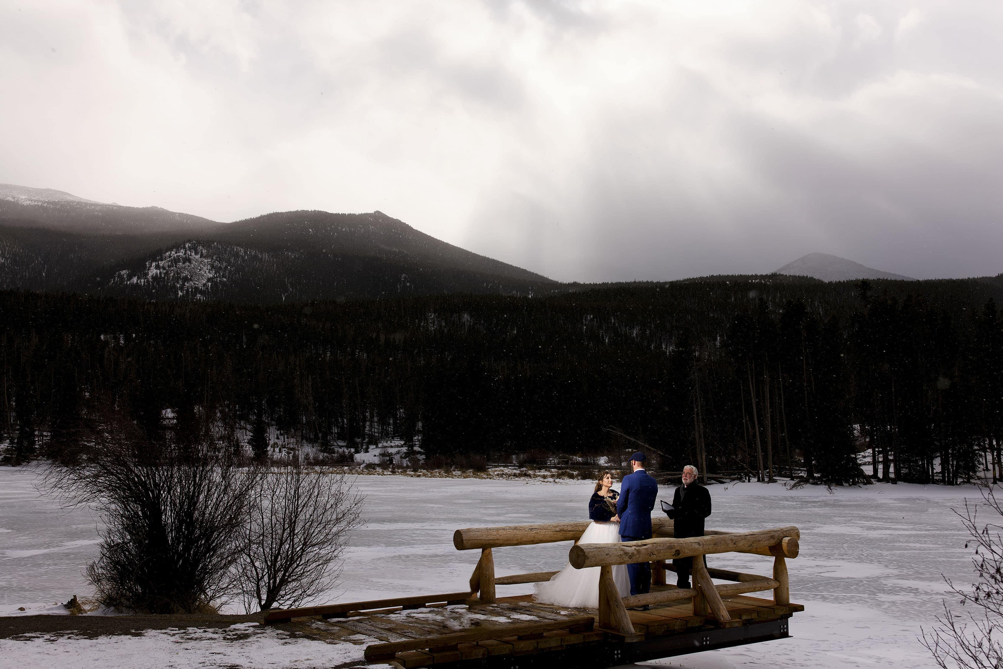 A couple stands on the bridge at Sprague Lake in Rocky Mountain National Park during their winter elopement