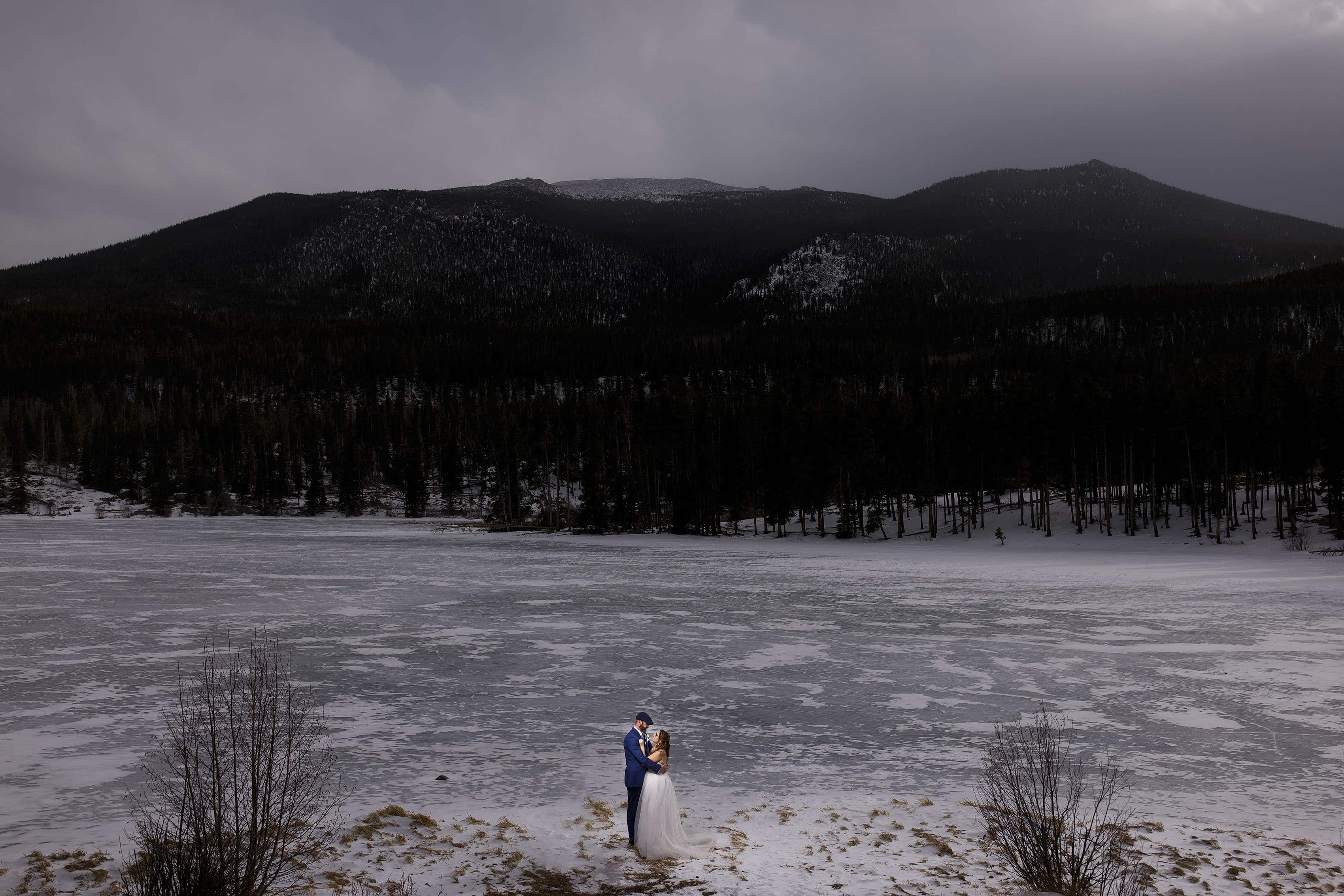 A couple share a moment together on frozen Sprague Lake during their winter elopement in Rocky Mountain National Park