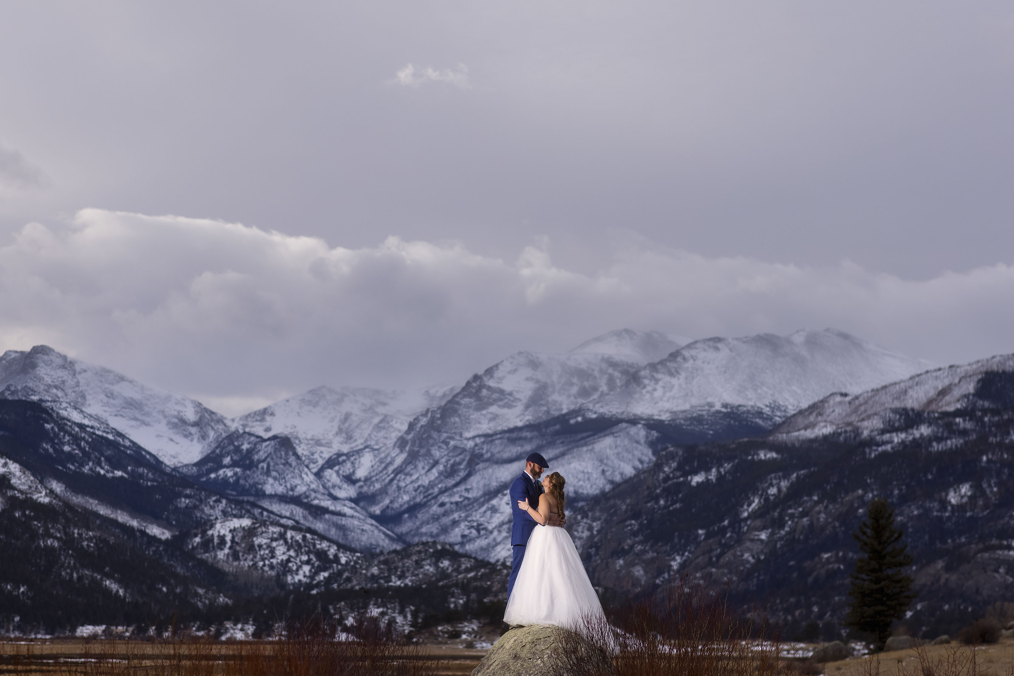 A couple share a moment together on a rock in Moraine Park in the valley at Rocky Mountain National Park during their winter elopement