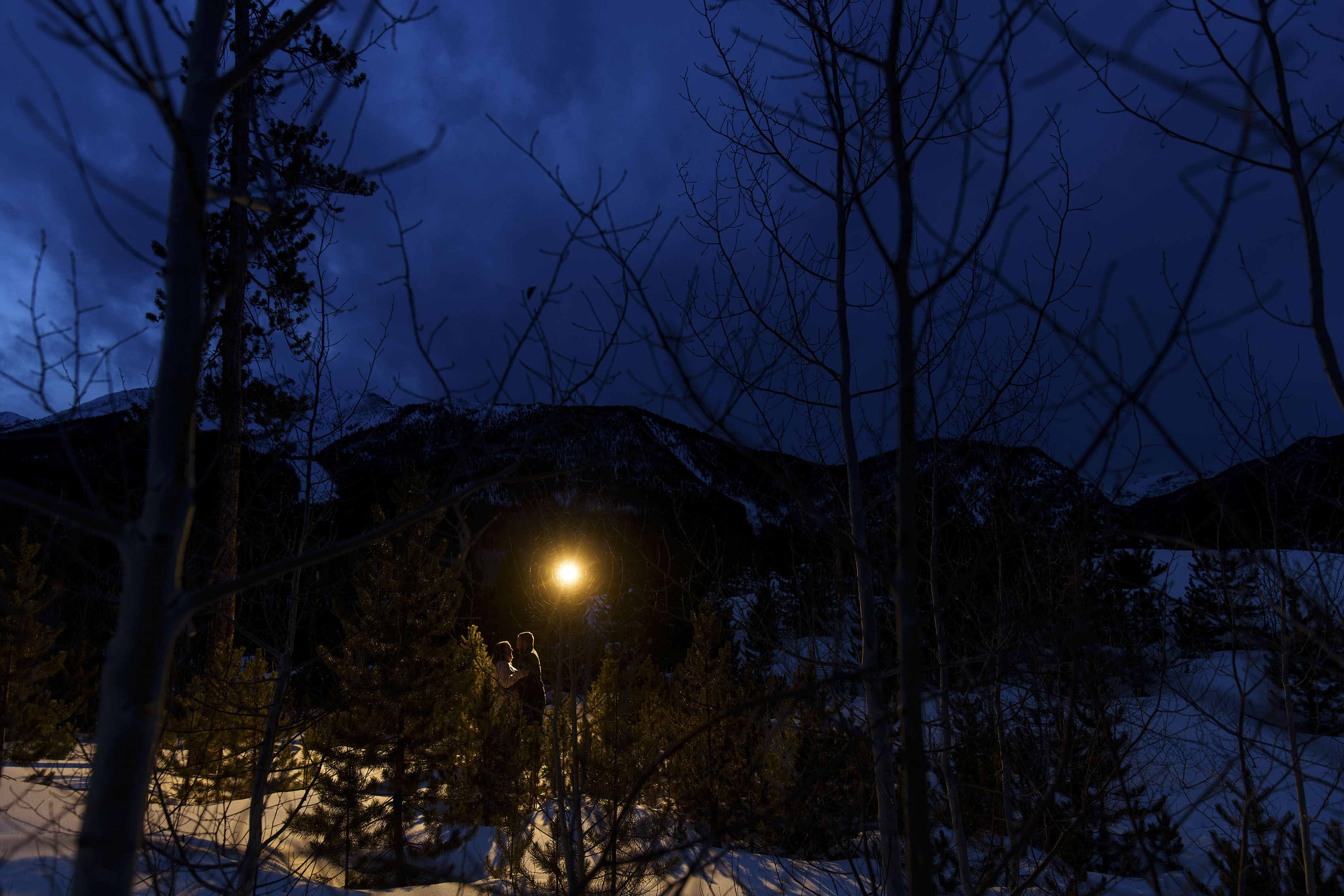 Nick and Bethany embrace at twilight in Frisco, Colorado
