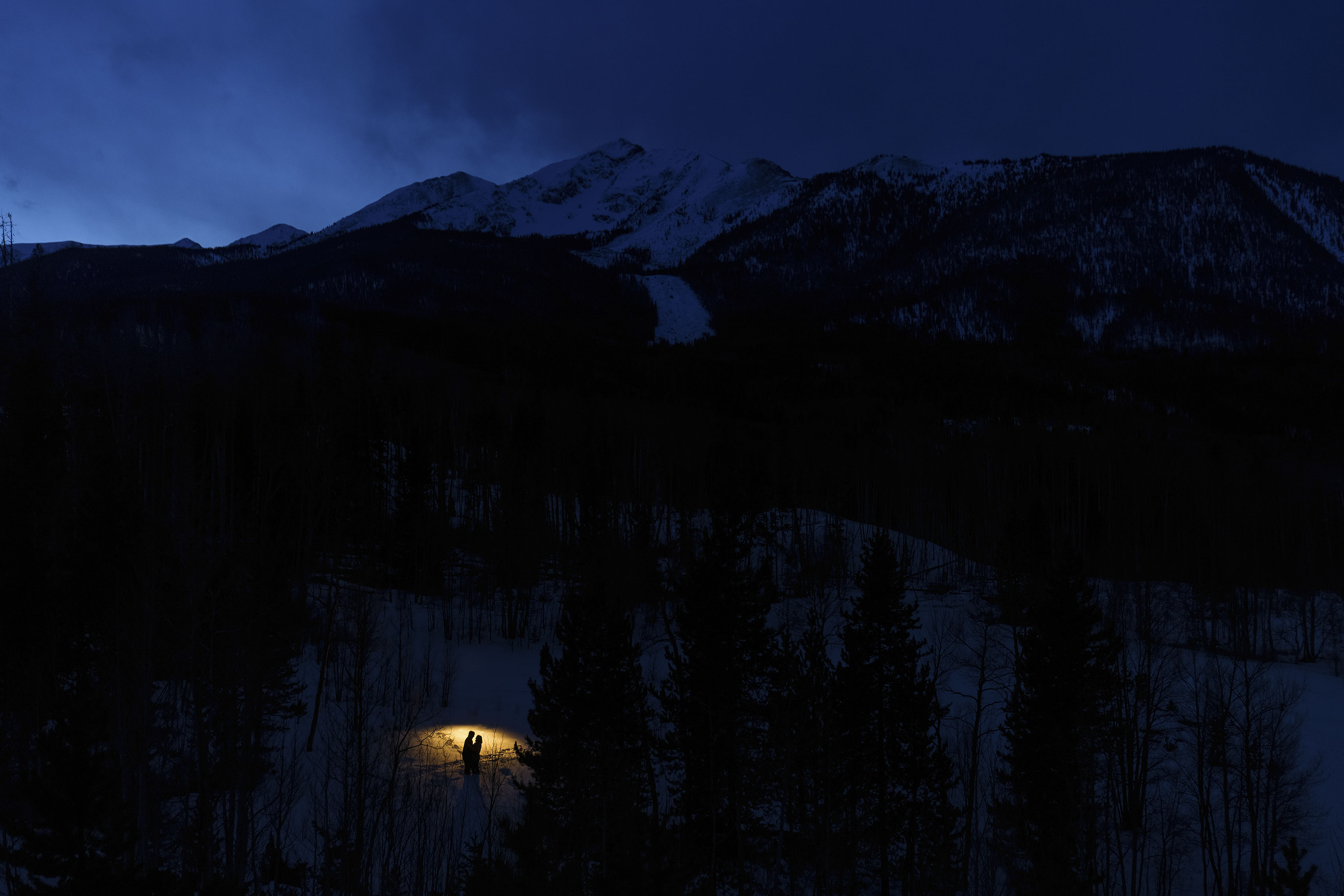 A couple is silhouetted against the snow during their engagement photos as twilight falls over Peak one in Frisco, Colorado