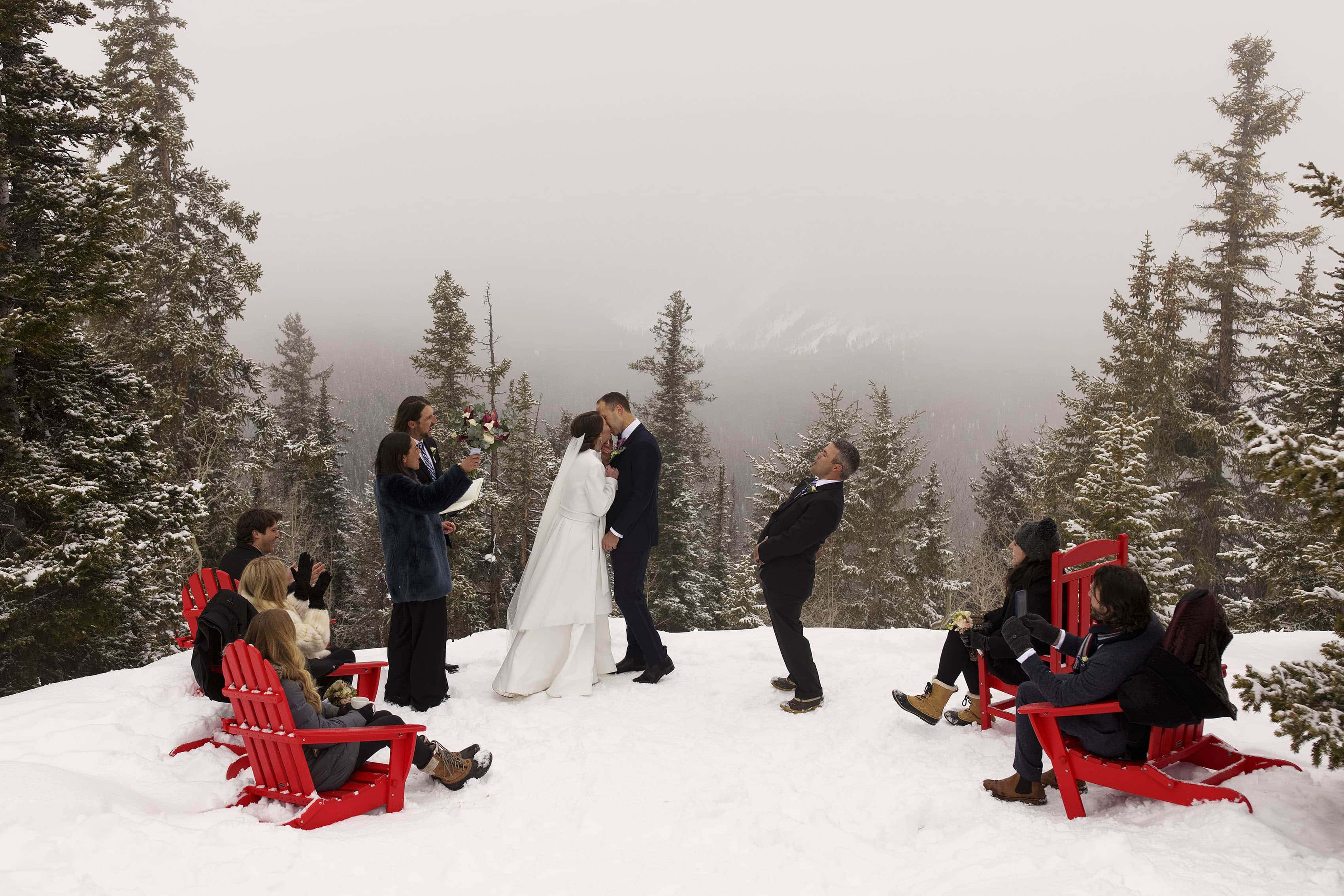 Olivia and Kyle's first kiss on the snowy Aspen wedding deck